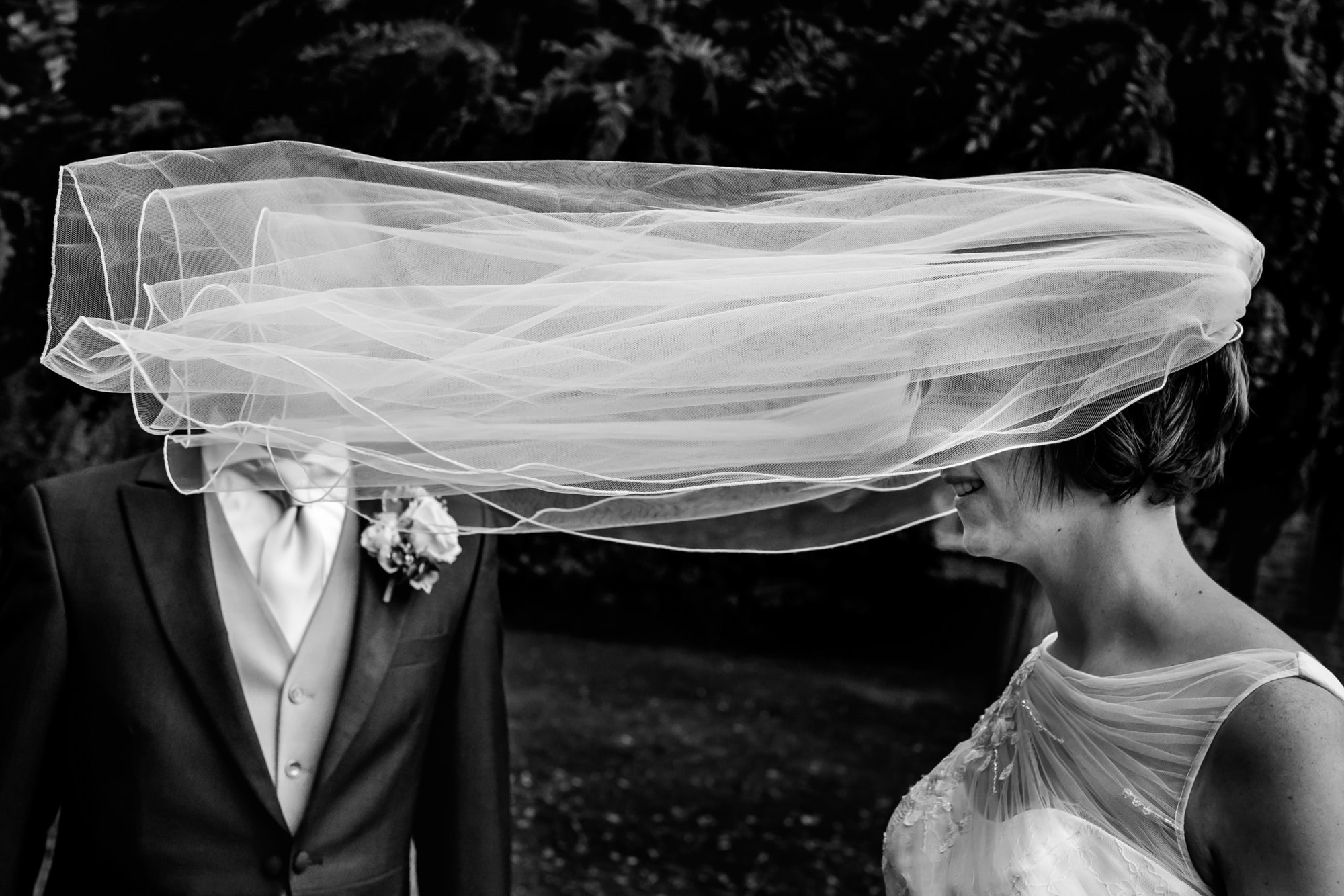Brides veil flies in front of grooms face - photo by Philippe Swiggers