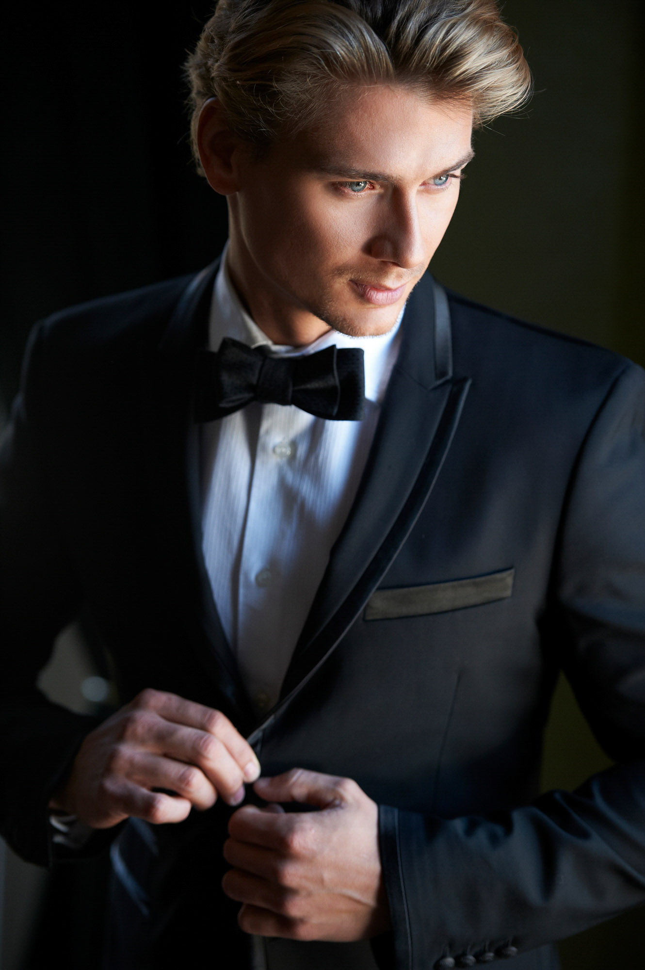 Blond groom wearing black tux with silk lapel - photo by Jerry Ghionis