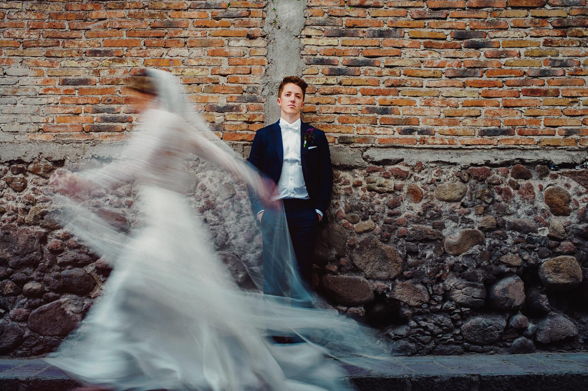 Long exposure portrait of bride walking past groom by Fer Juaristi