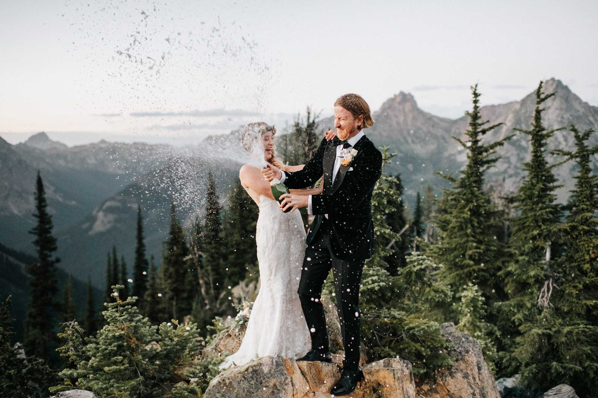 Couple pops champagne on mountain top - Nick + Danee
