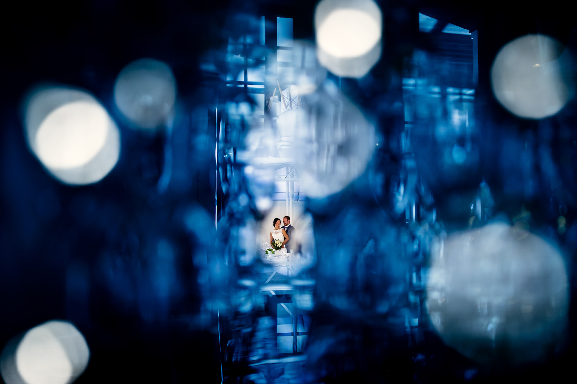 Creative couple portrait with bokeh blue glass artifacts by Eppel Fotographie
