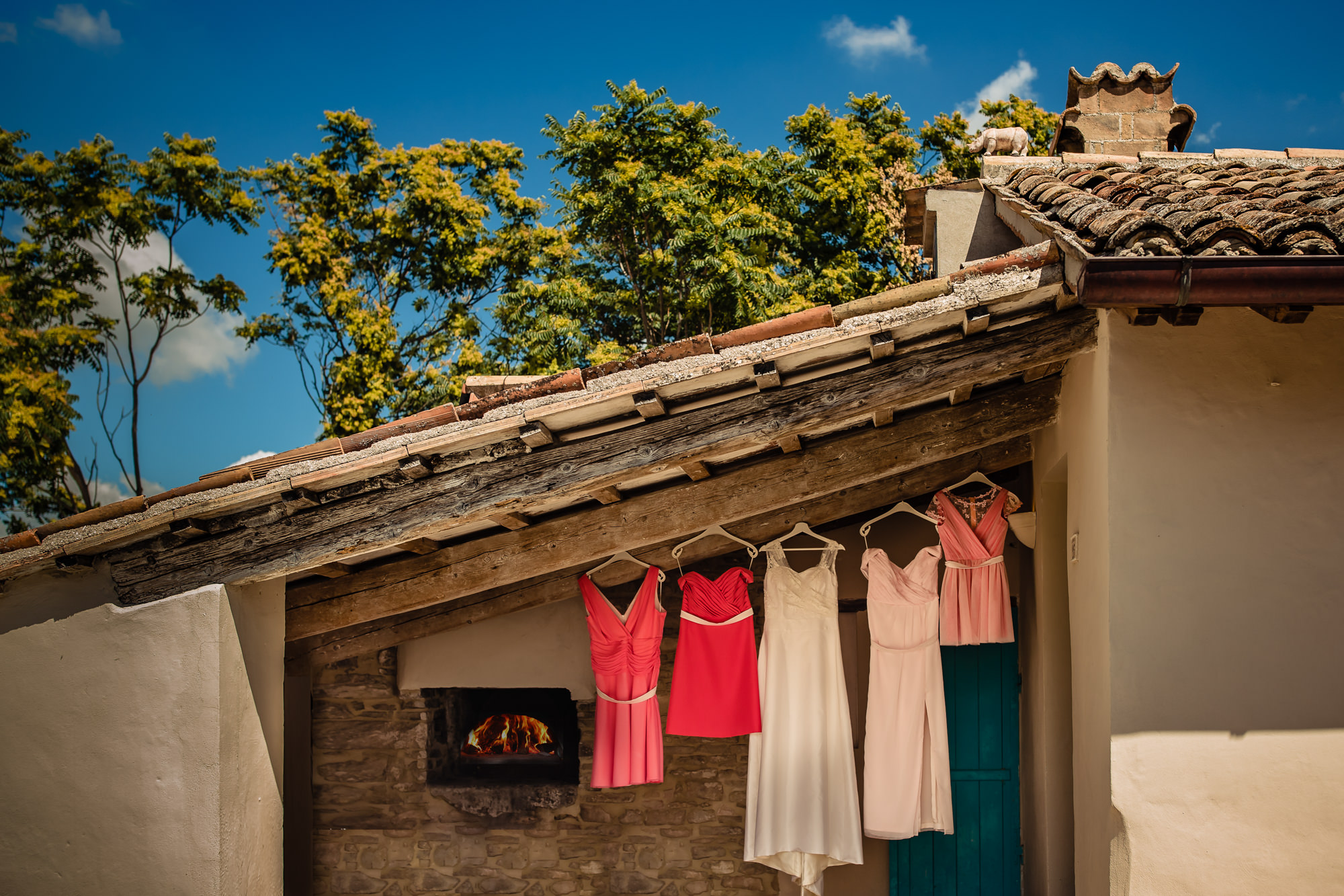 Creative photo of bridesmaids dresses hanging under roof with window framing bride getting ready by Eppel Fotographie