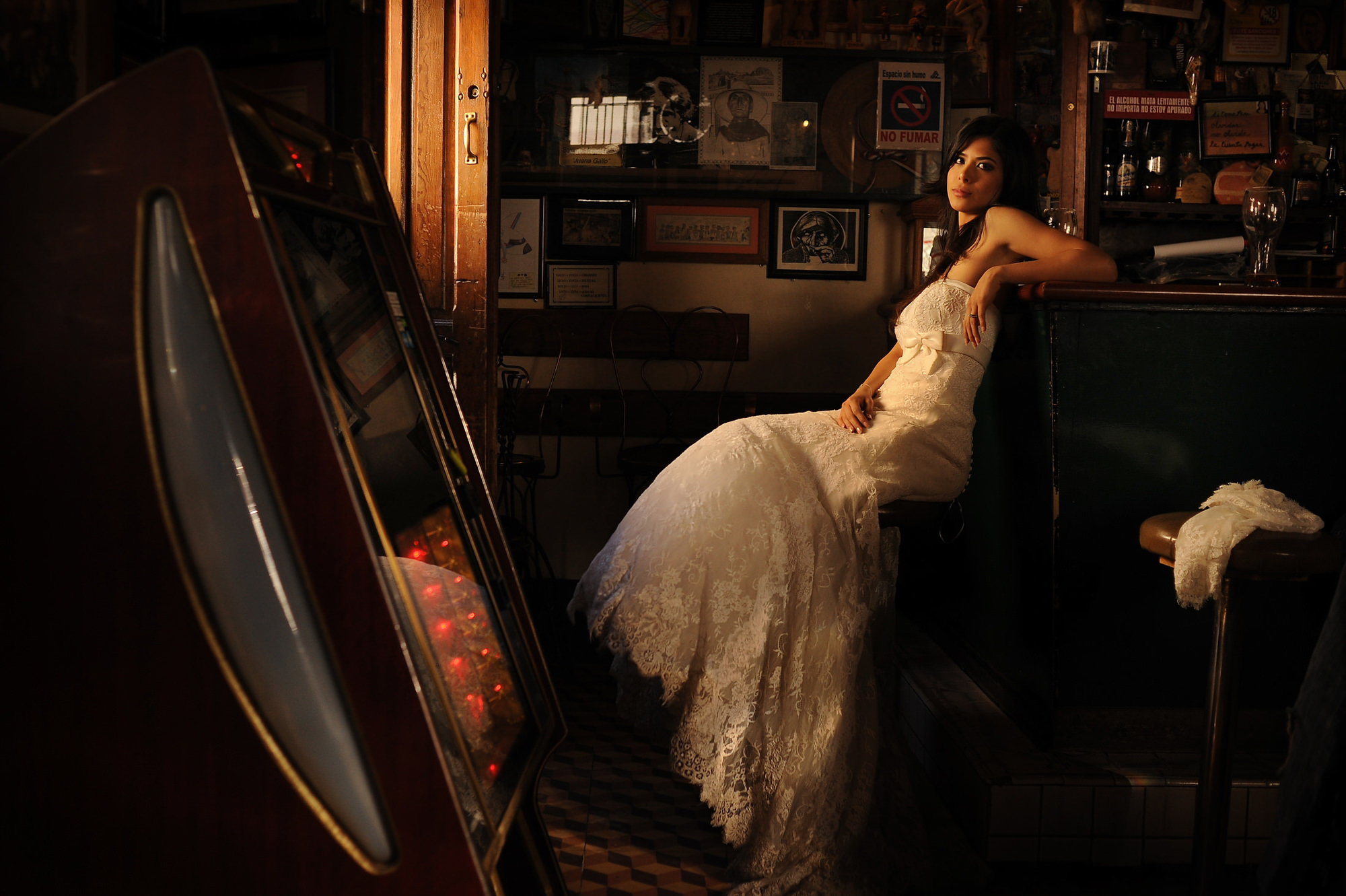 Bridal portrait in bar with jukebox lace gown - photo by Daniel Aguilar