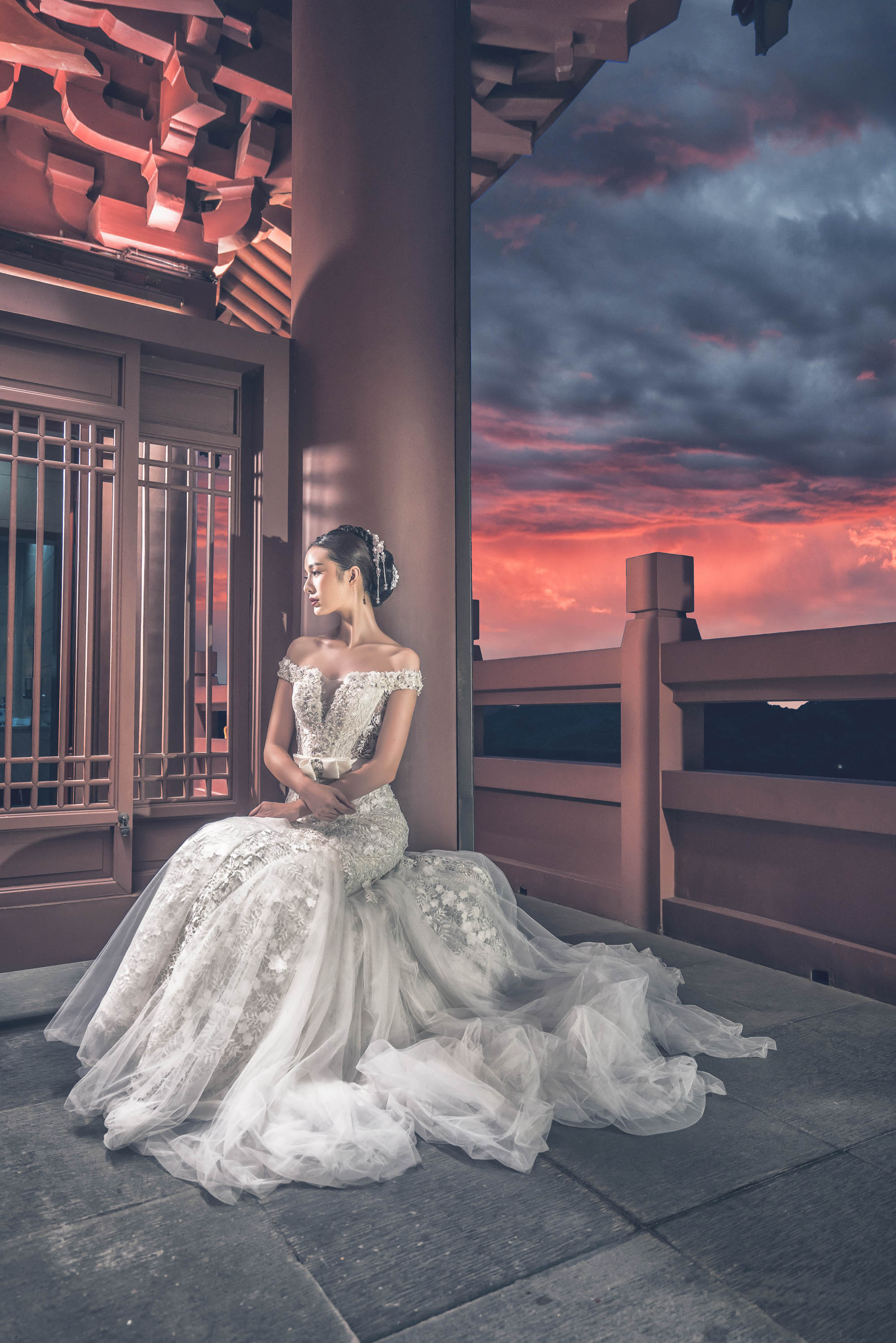 Bride in off-shoulder beaded gown sitting at Chinese temple during sunset, by CM Leung