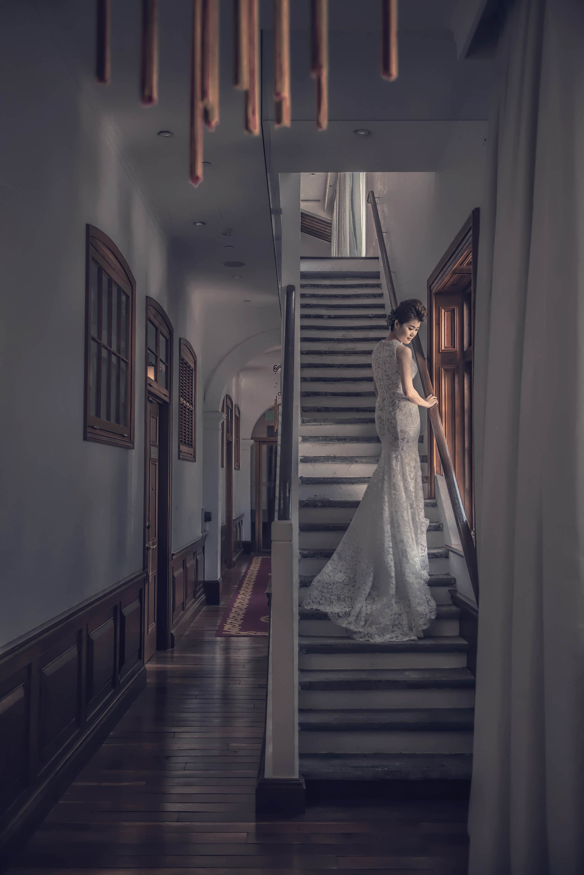Bride standing on stairs in trumpet lace gown, by CM Leung