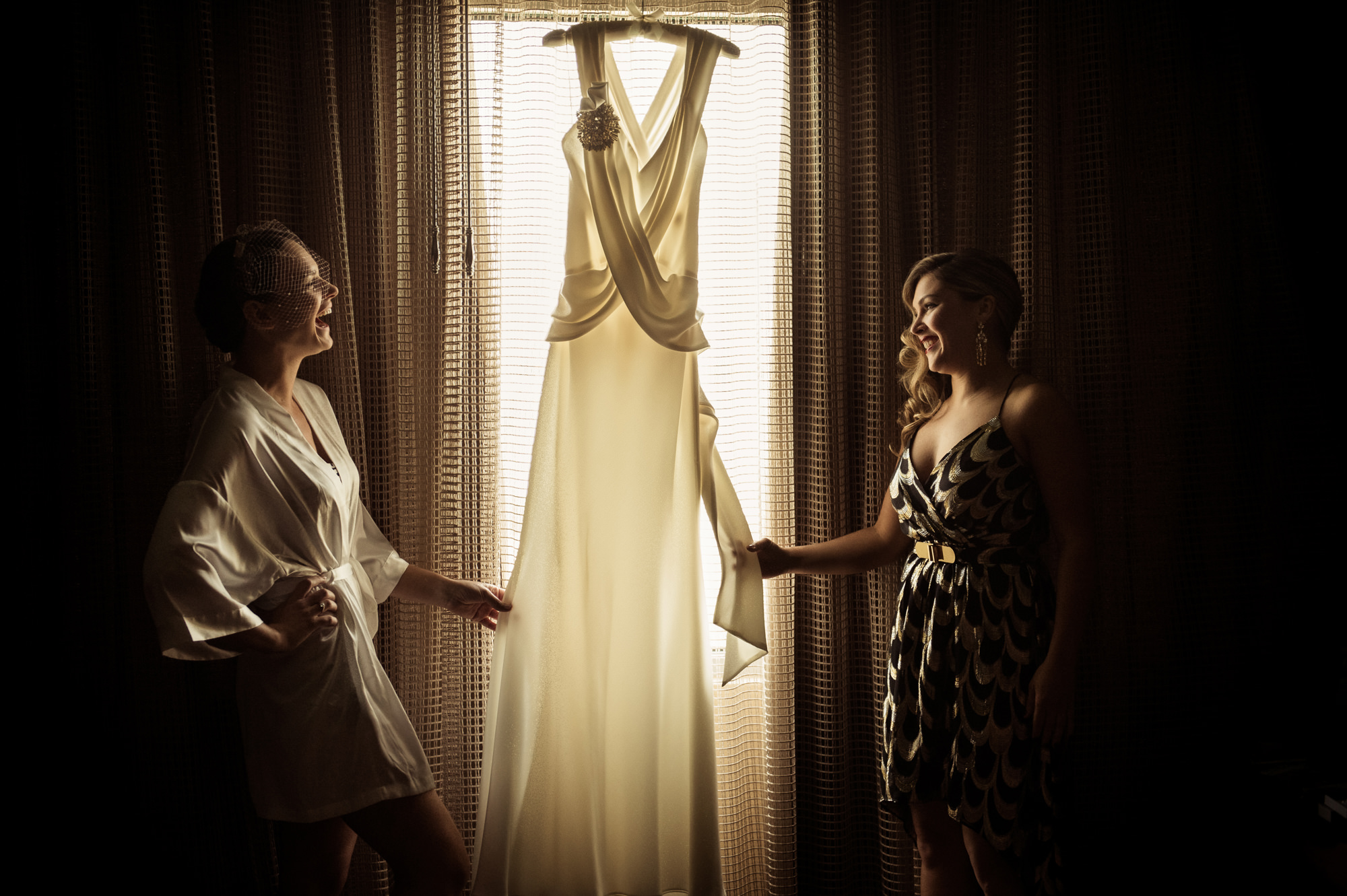 Bride and bridesmaid laughing holding beautiful crepe gown, by Cliff Mautner