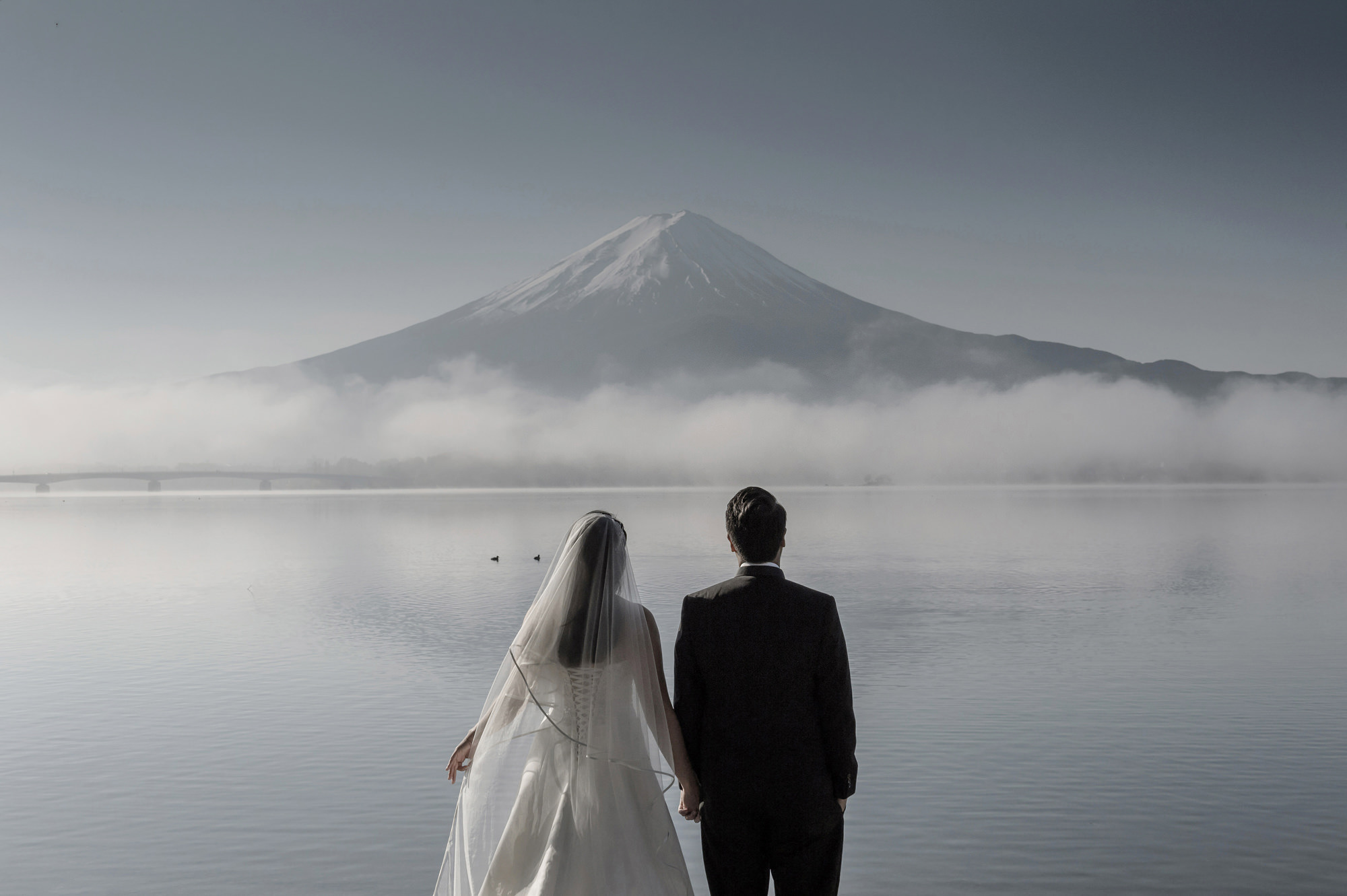 Bride and groom look out at Mt. Fuji - photo by 37 Frames - Japan