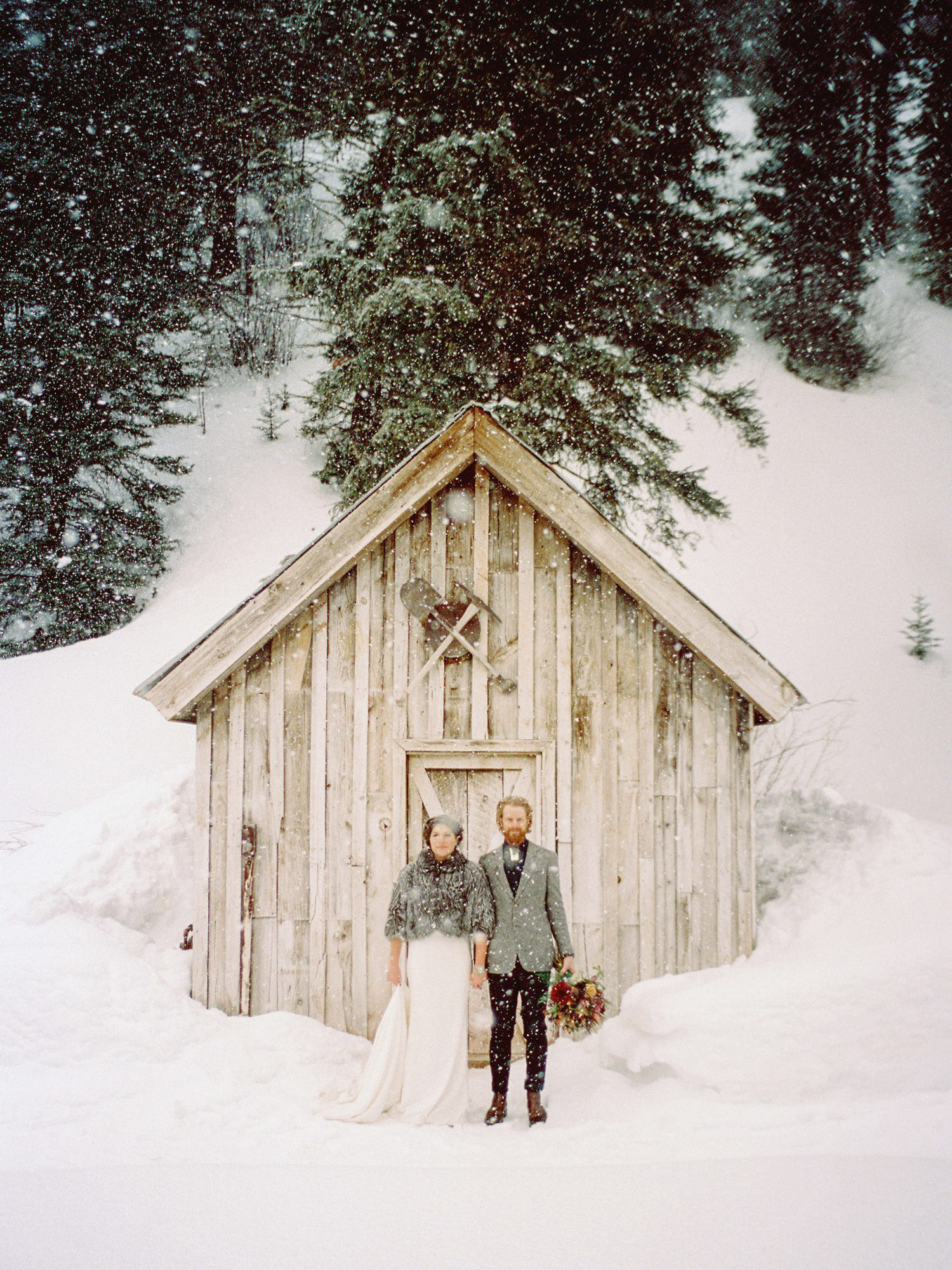 Bride in faux fur coat and groom in grey suit winter portrait in the snow, photo by Benj Haisch