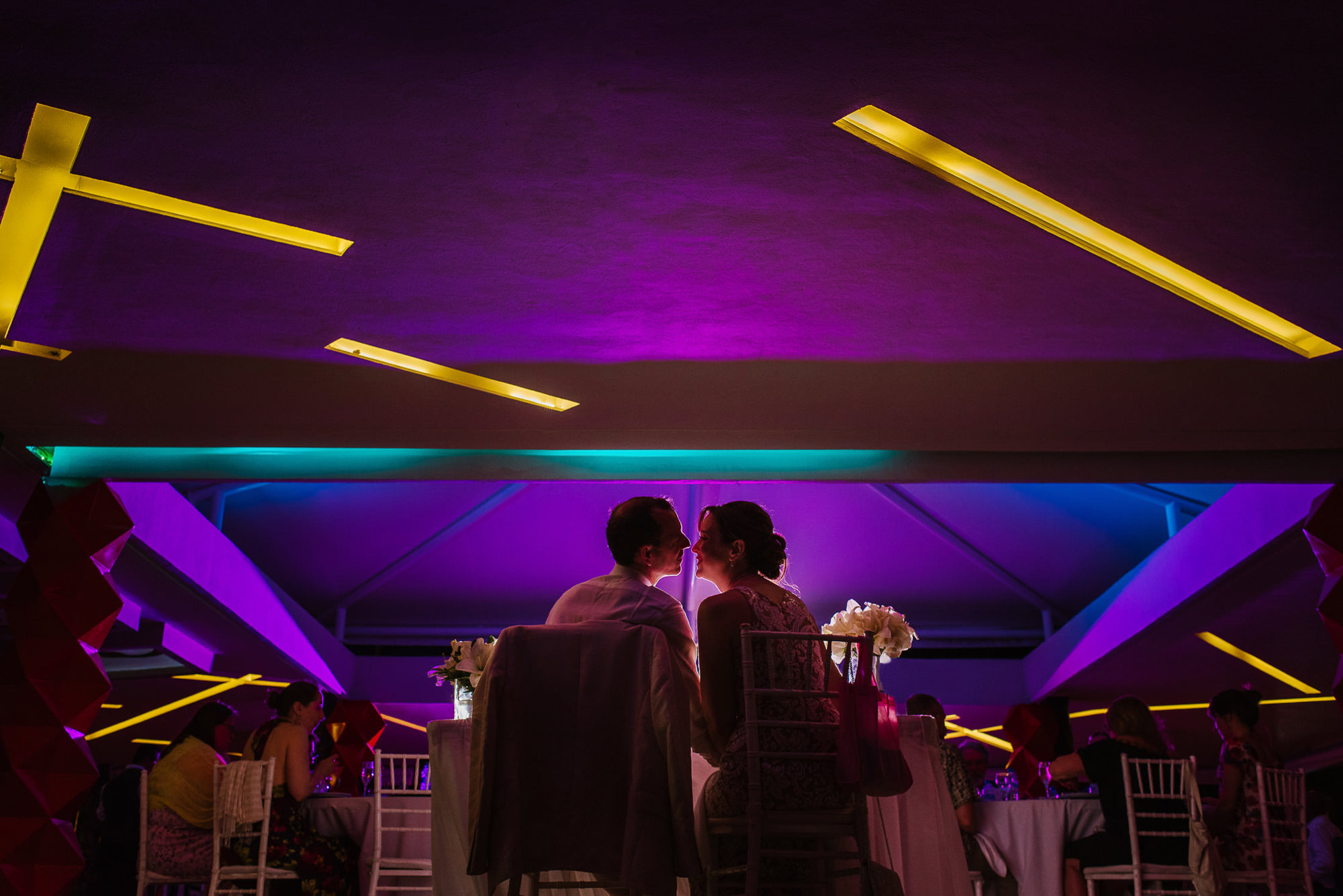 Bride and groom kiss at sweetheart table, with neon lights, by Citlalli Rico