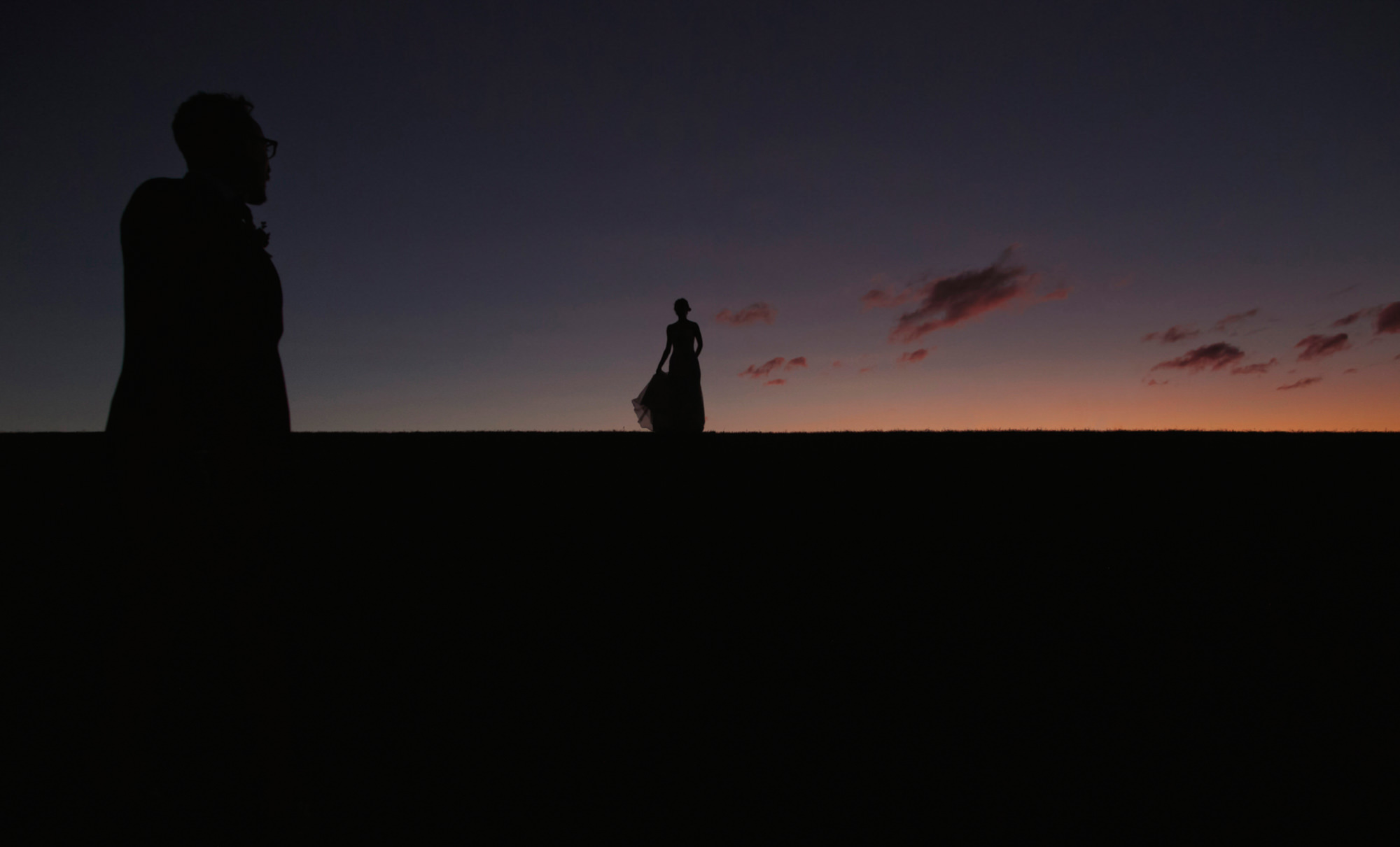 Silhouette of bride in the distance with groom in foreground, by Dan O' Day