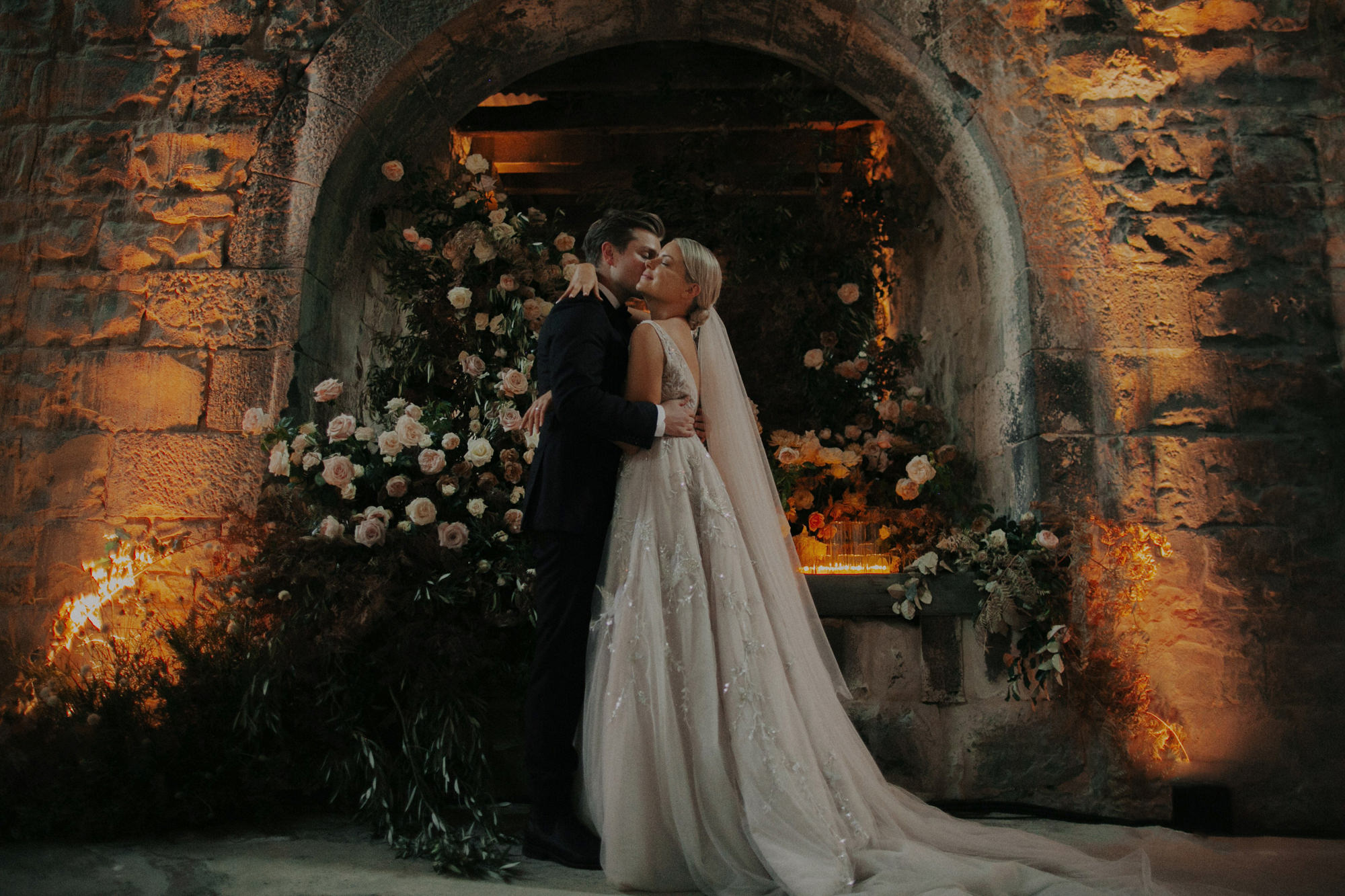 Bride and groom embrace in front of floral arch  - photo by Dan O'Day