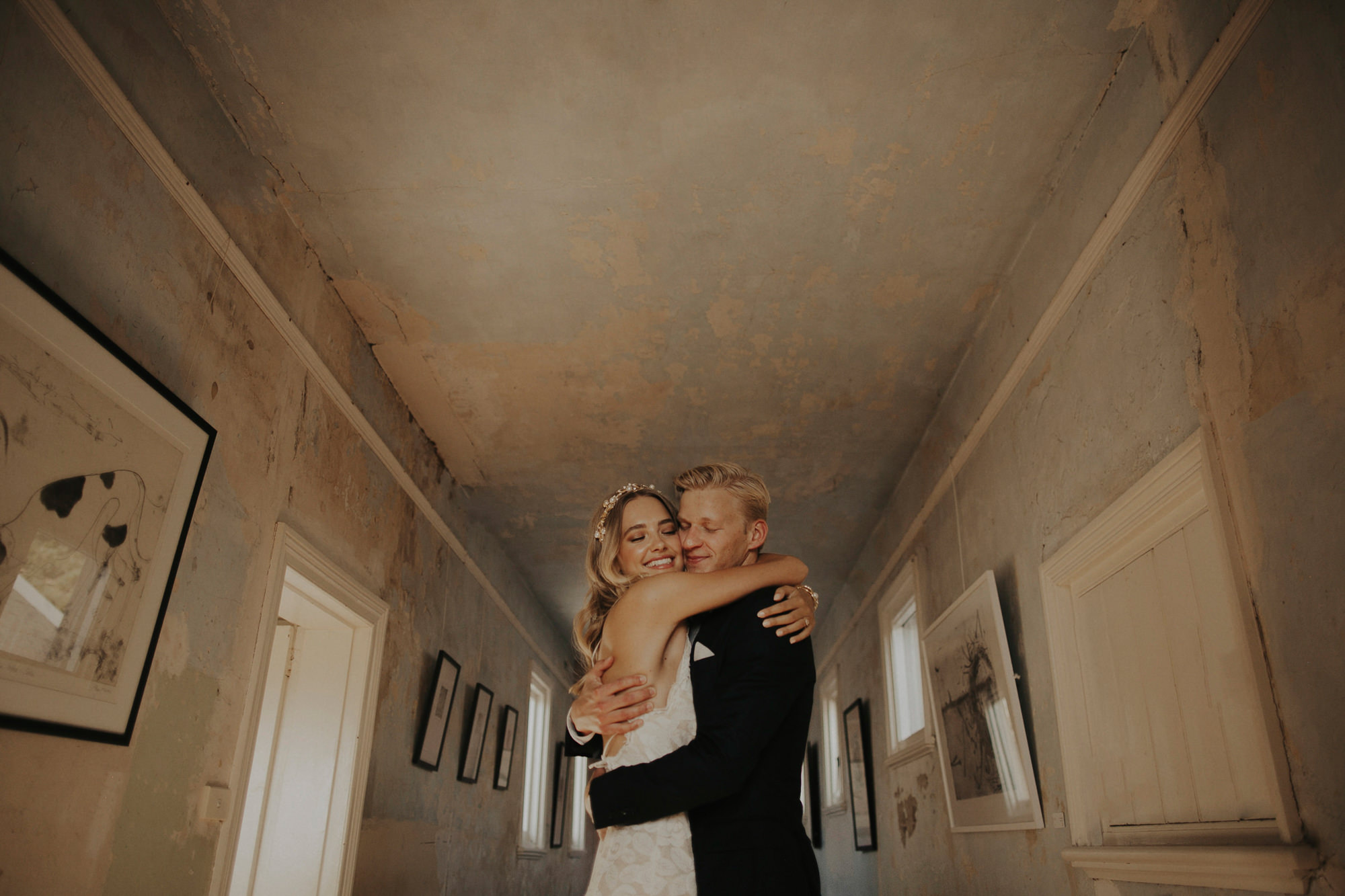 Bride and groom embrace in hallway  - photo by Dan O'Day