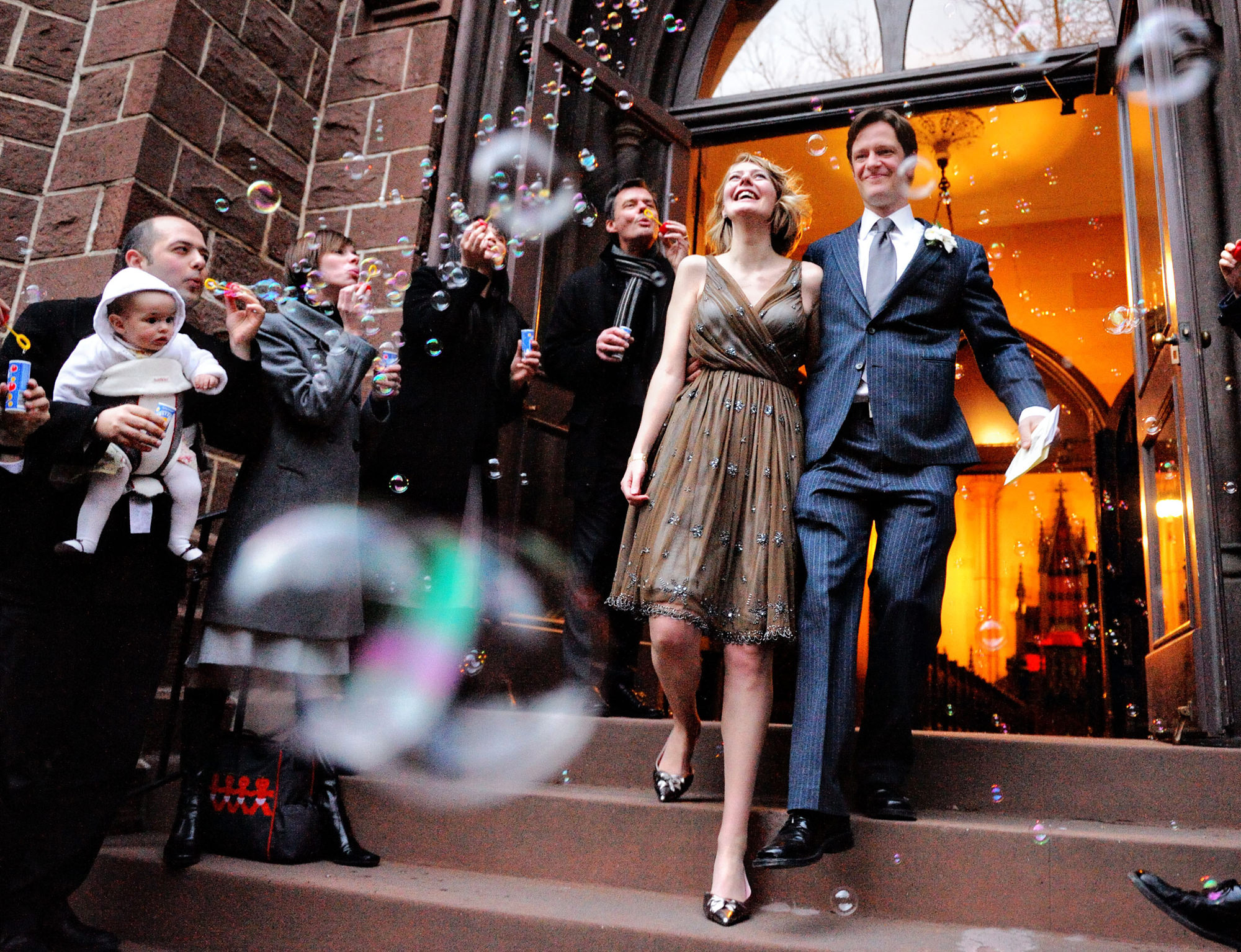 Bride and groom bubble exit from church, by the Brenizers