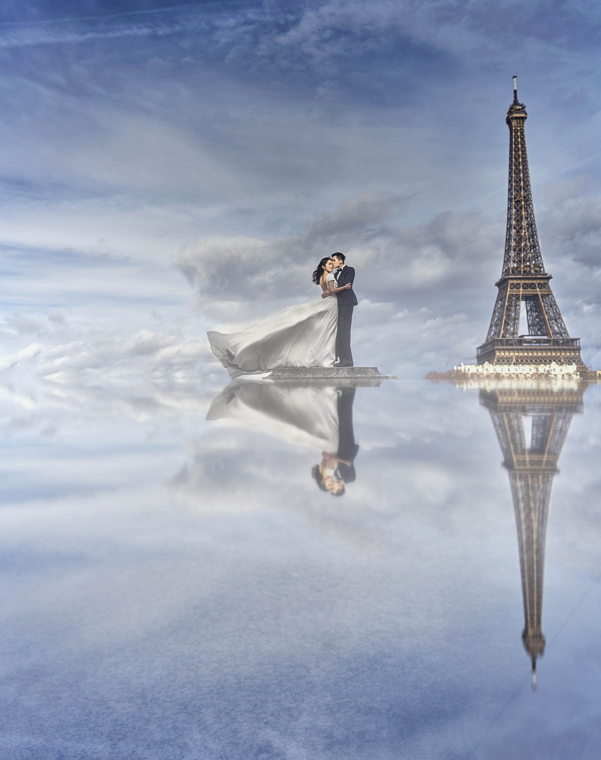 Bride in beautiful satin ballgown and groom in tuxedo by Eiffel Tower, by CM Leung