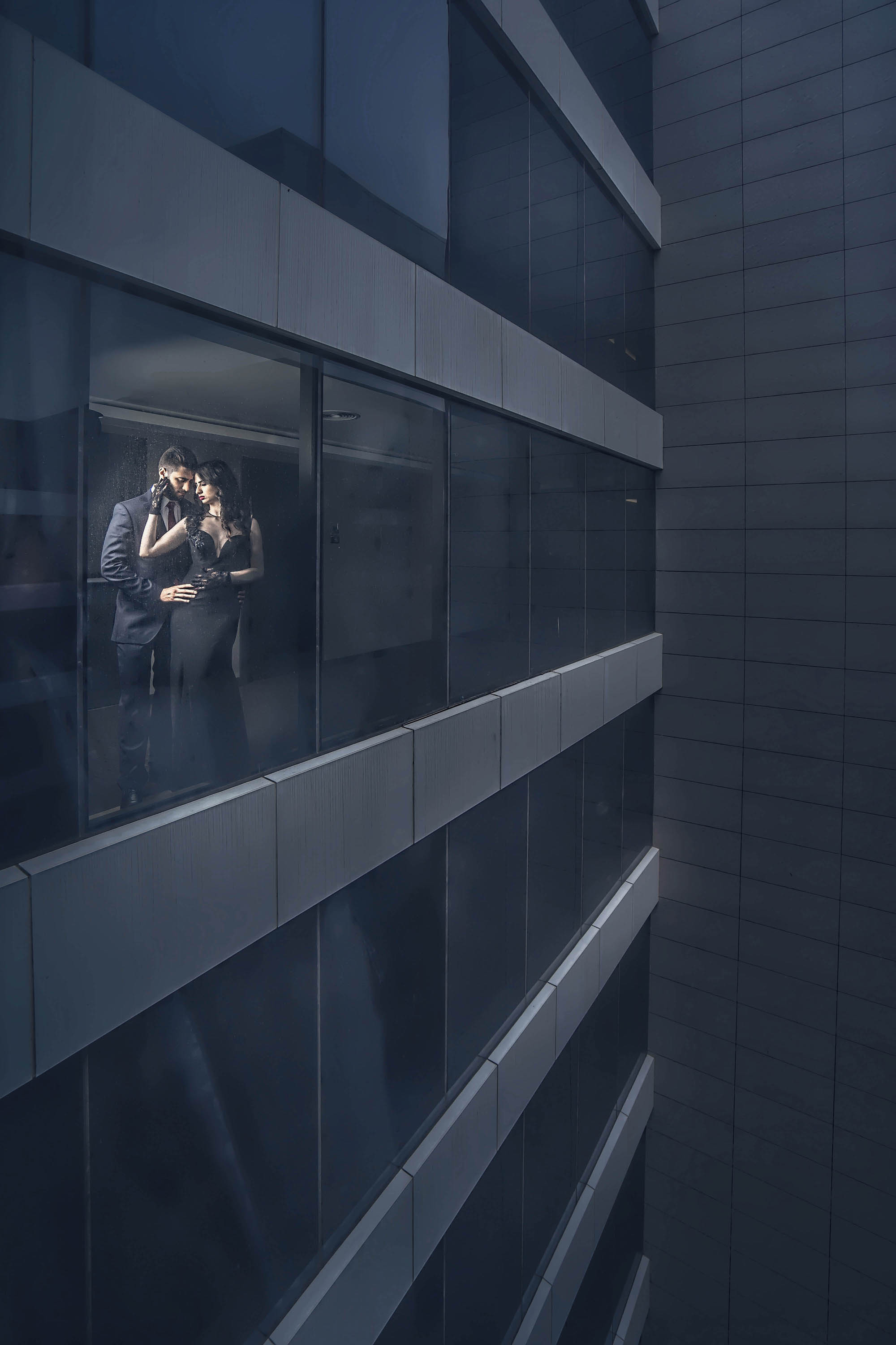 Bride and groom in black, in office building shot from outside