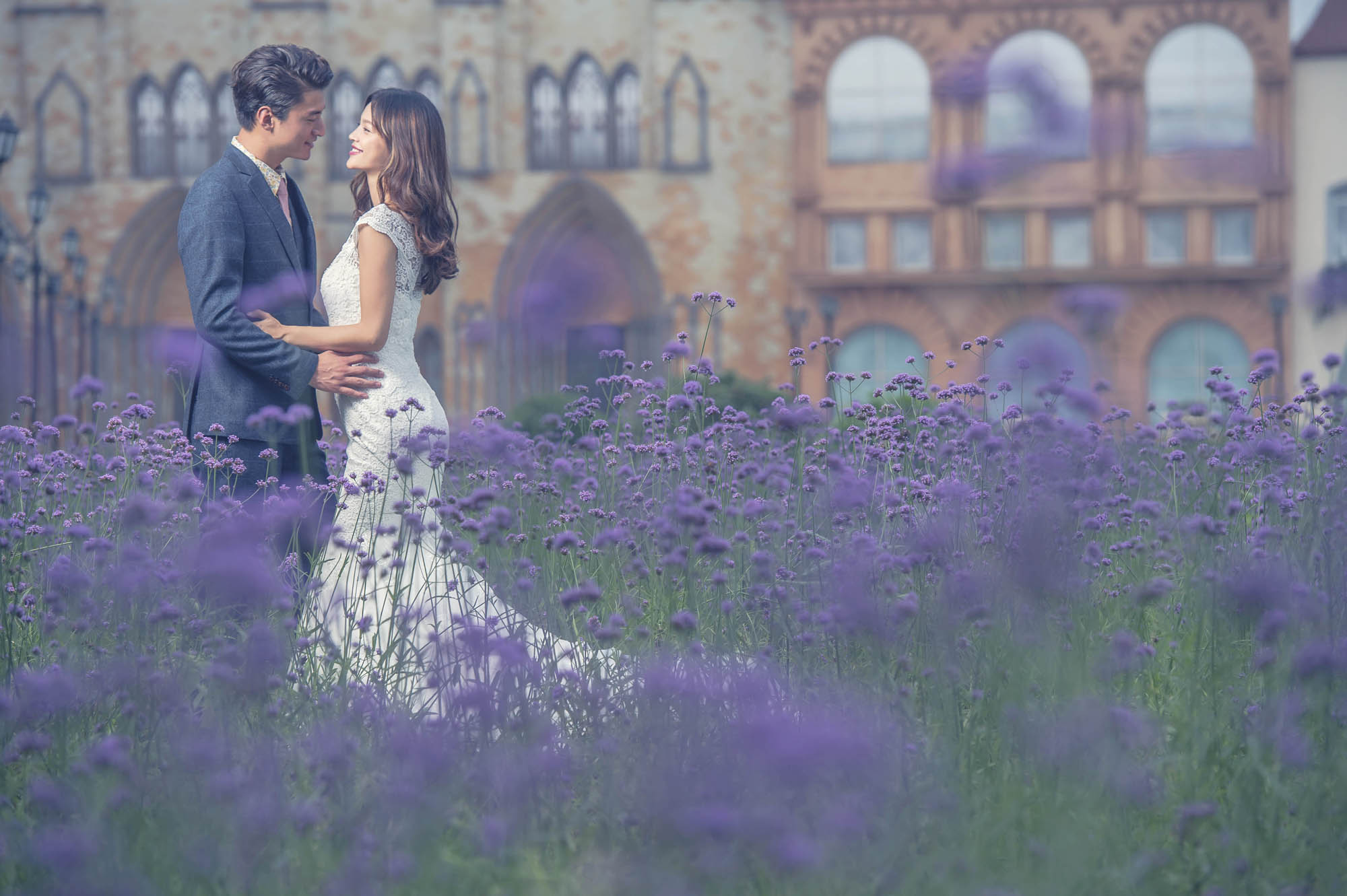 Bride and groom in field of purple flowers, by CM Leung