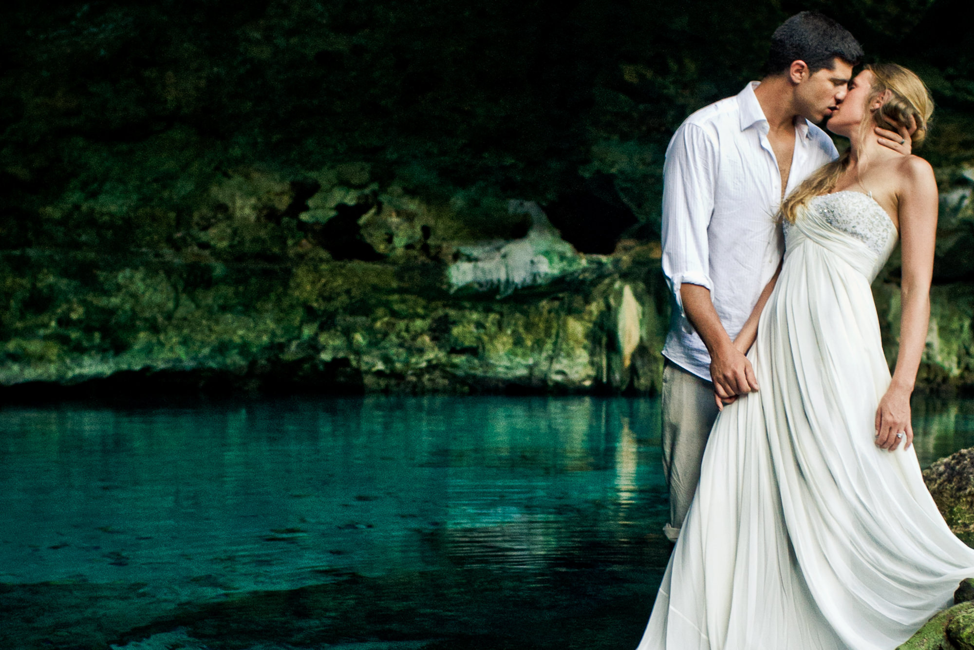 Bride and groom kiss by cenote - photo by JAG Studios