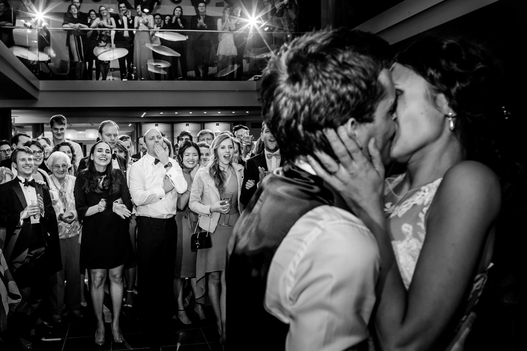 Bride and groom kiss while guests cheer - photo by Philippe Swiggers