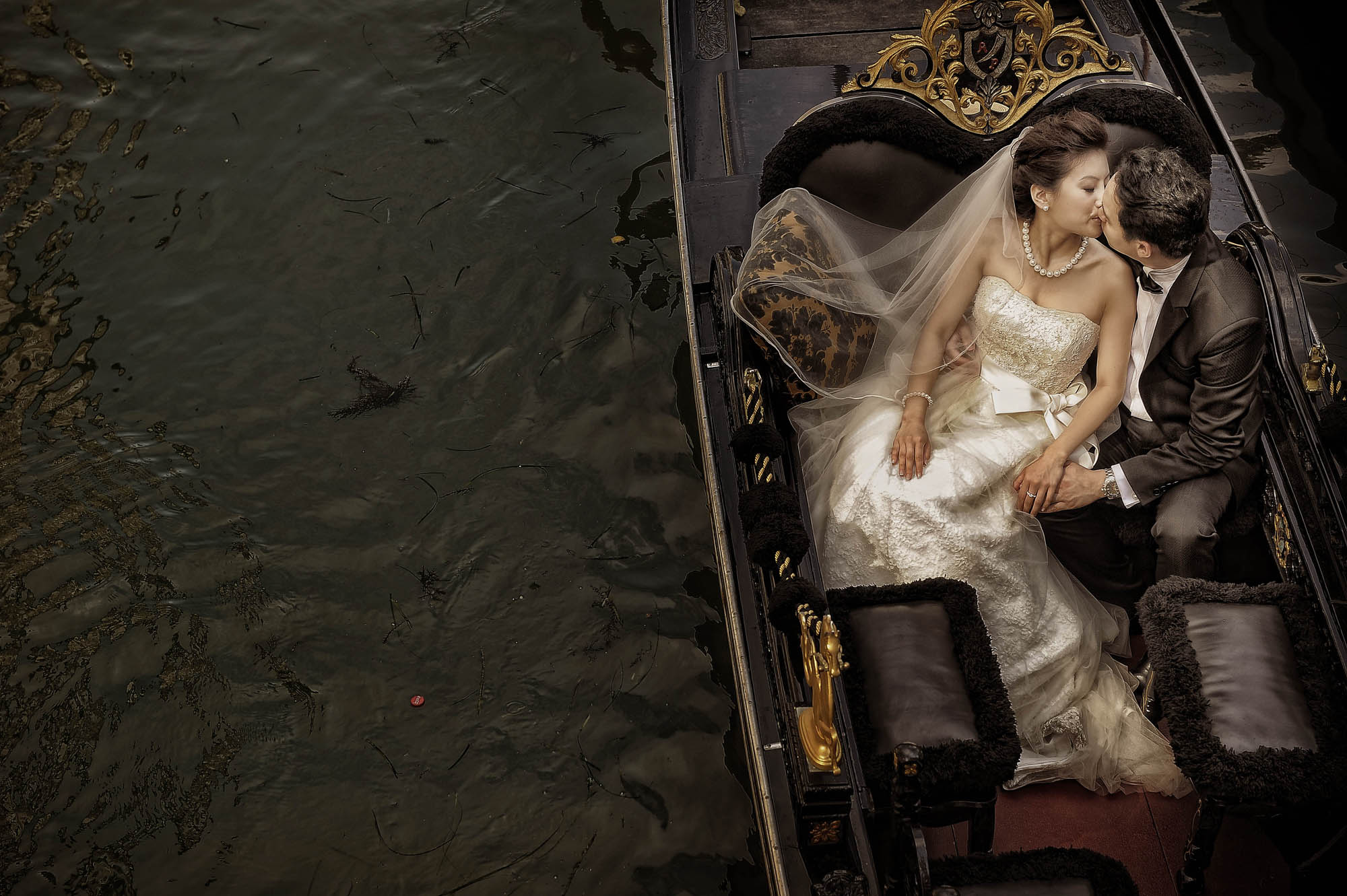 Bride and groom kissing in gondola, by CM Leung