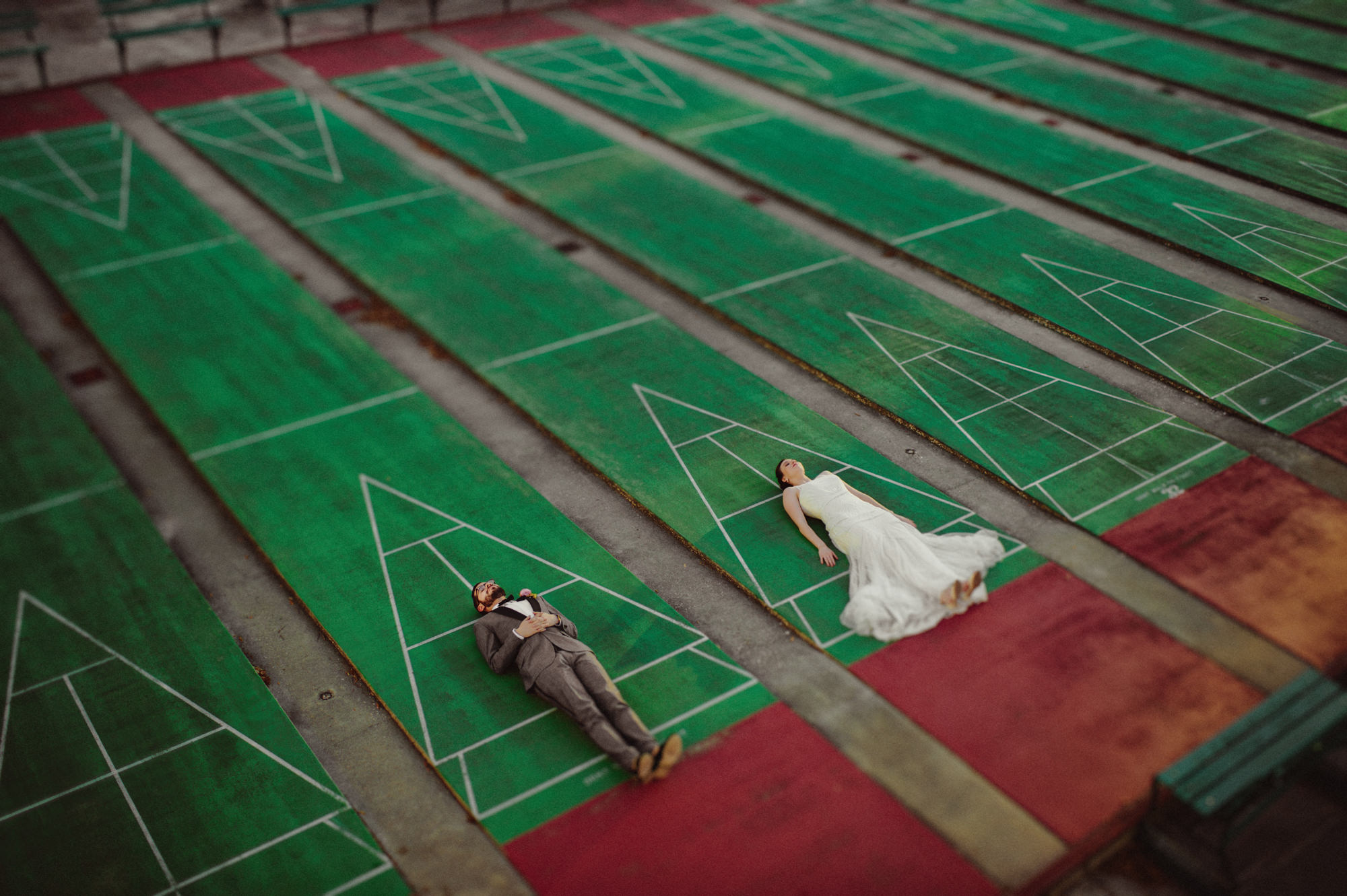 Bride and groom lying on bowling green by Fer Juaristi