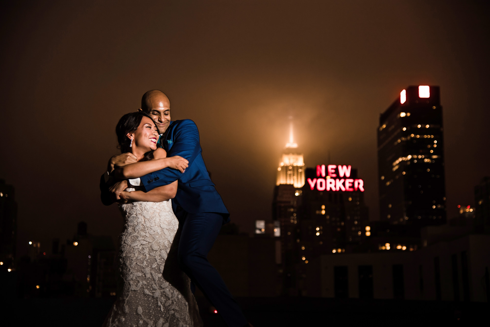 Asian bride and groom hug with New Yorker building in background, by Cliff Mautner