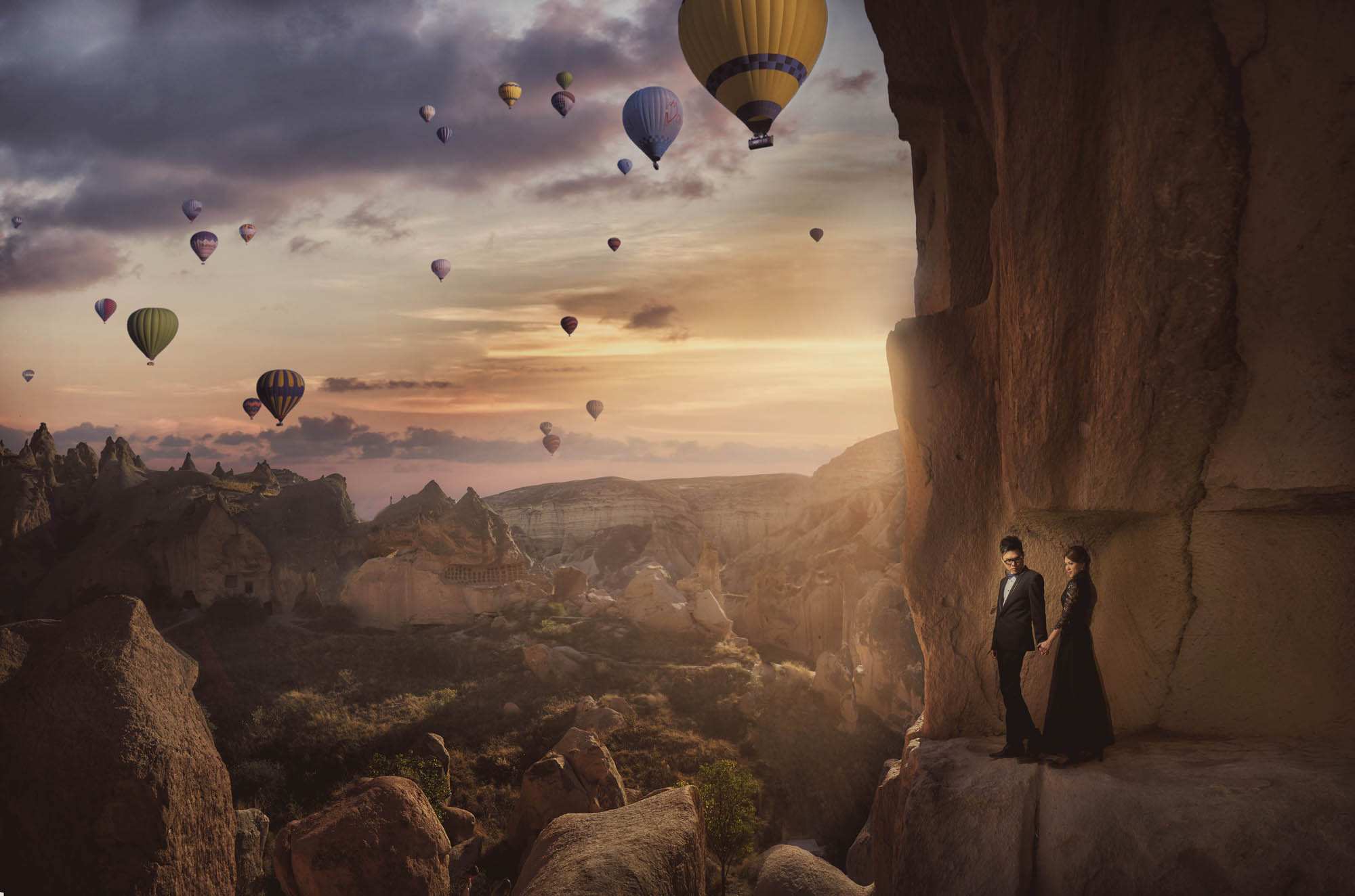 Bride and groom in black, standing at cliff with hot air balloons in distance, by CM Leung