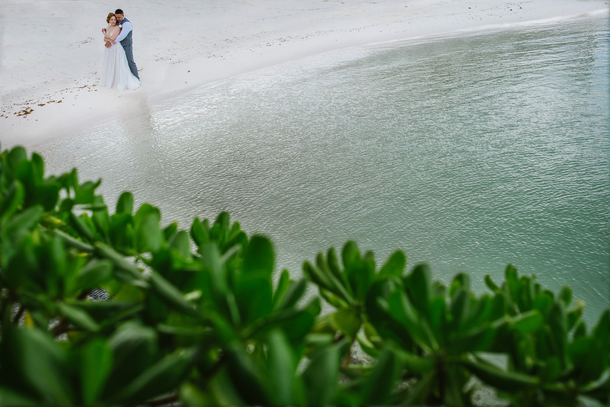 Bride and groom pose next to water on beach, by Citlalli Rico