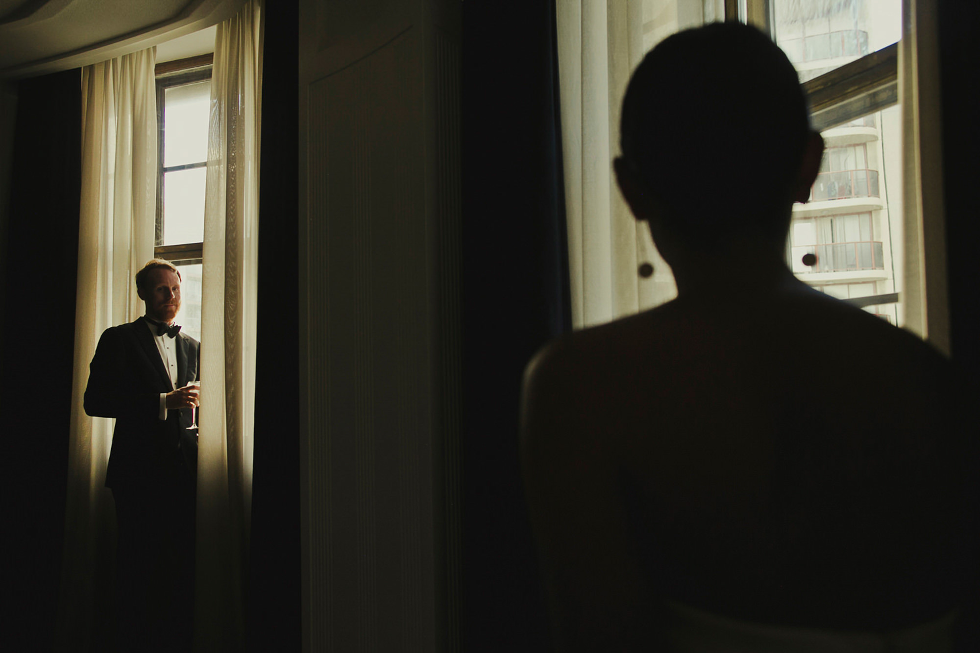 Groom portrait by window with silhouette in forefront - photo by Dan O'Day