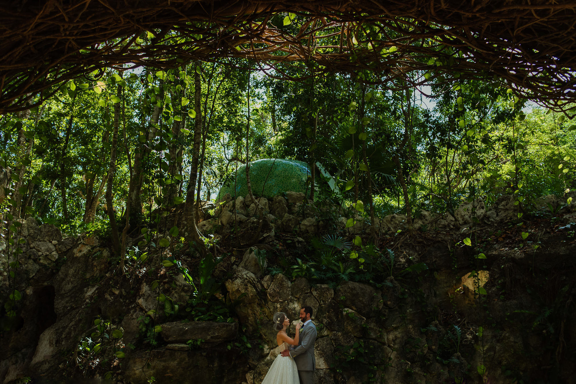 Bride and groom in cenote with lush forest around, by Citlalli Rico