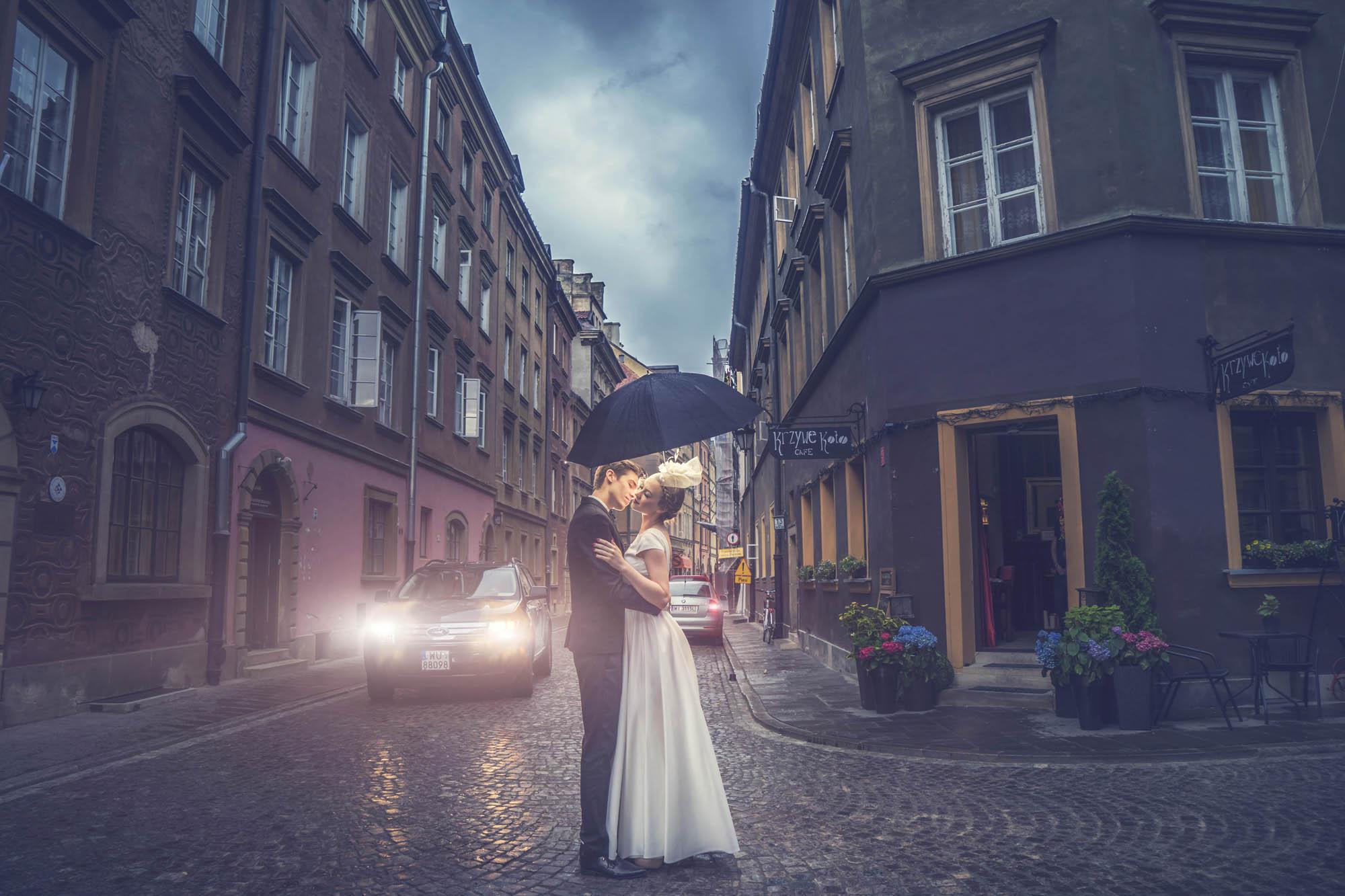 Bride and groom under umbrella in quaint village setting, by CM Leung