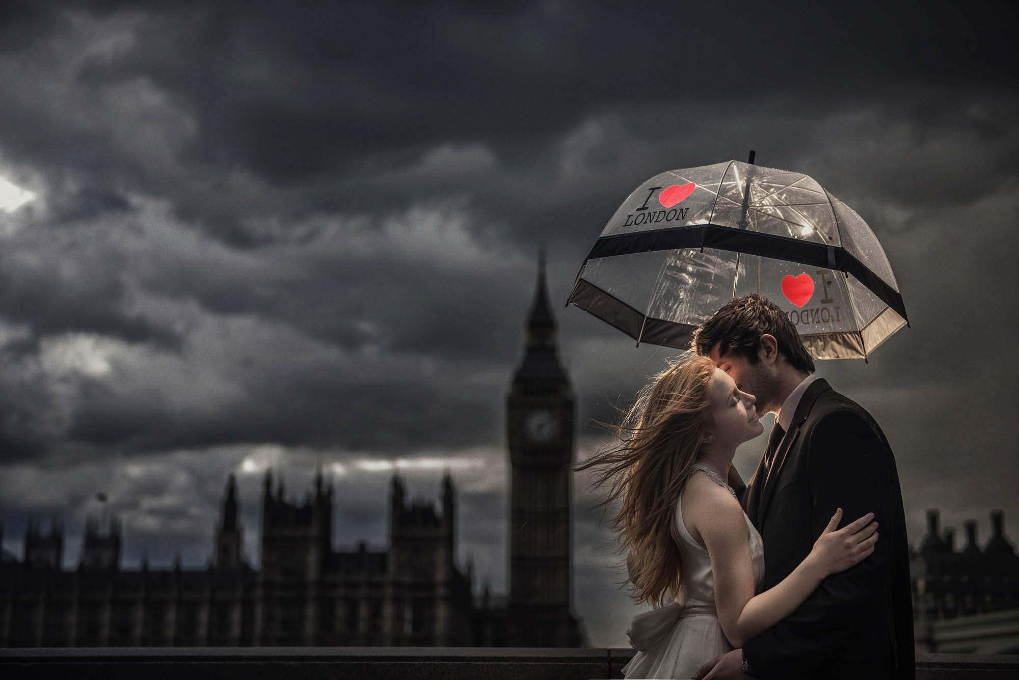 Bride and groom under I  Love London umbrella with Big Ben in background, by CM Leung