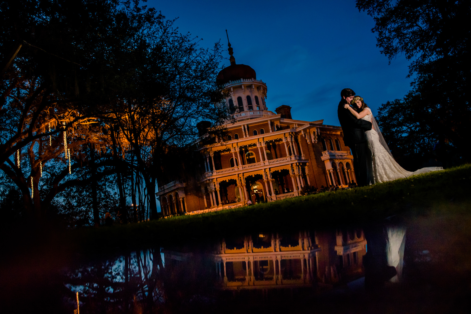 Bride and groom portrait at dusk in front of historic building, by Chrisman Studios