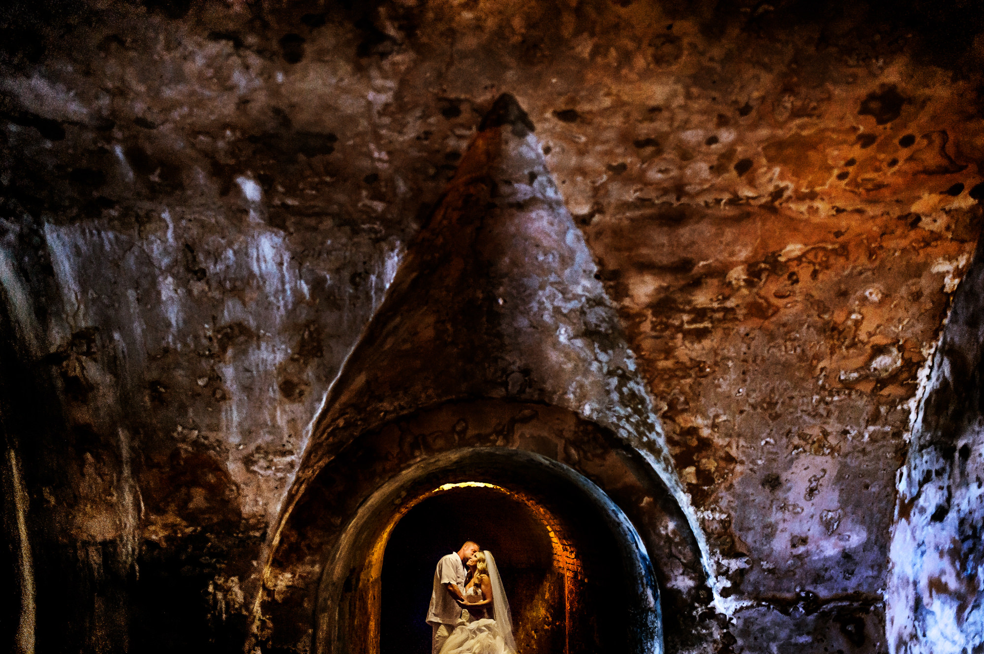 Couple framed in rustic ruins doorway, by Chrisman Studios