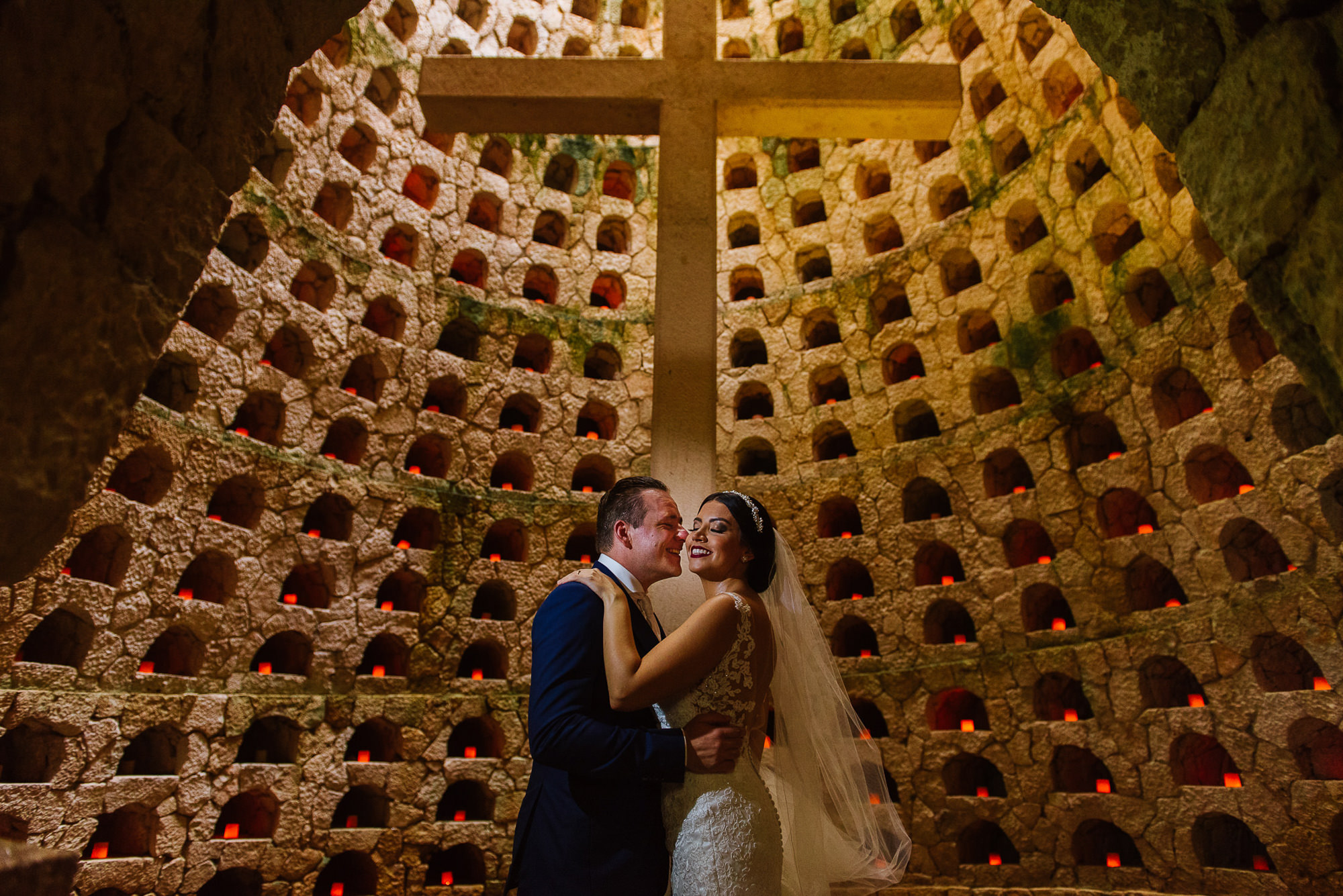 Bride and groom pose in front of cross in underground church, by Citlalli Rico