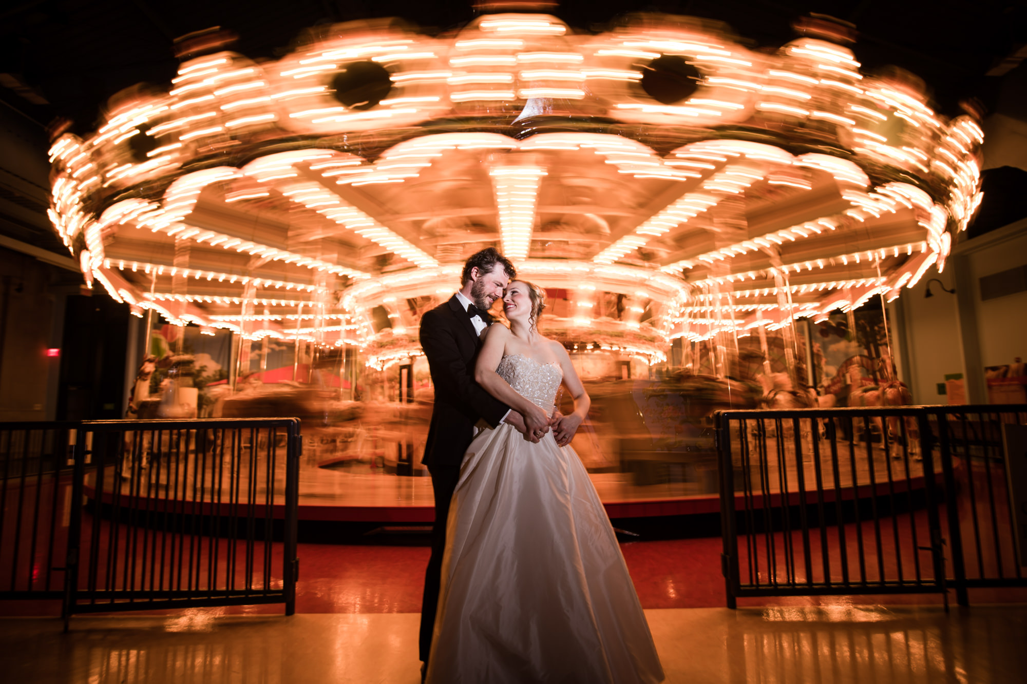 Bride and groom pose in front of spinning carousel, by Cliff Mautner