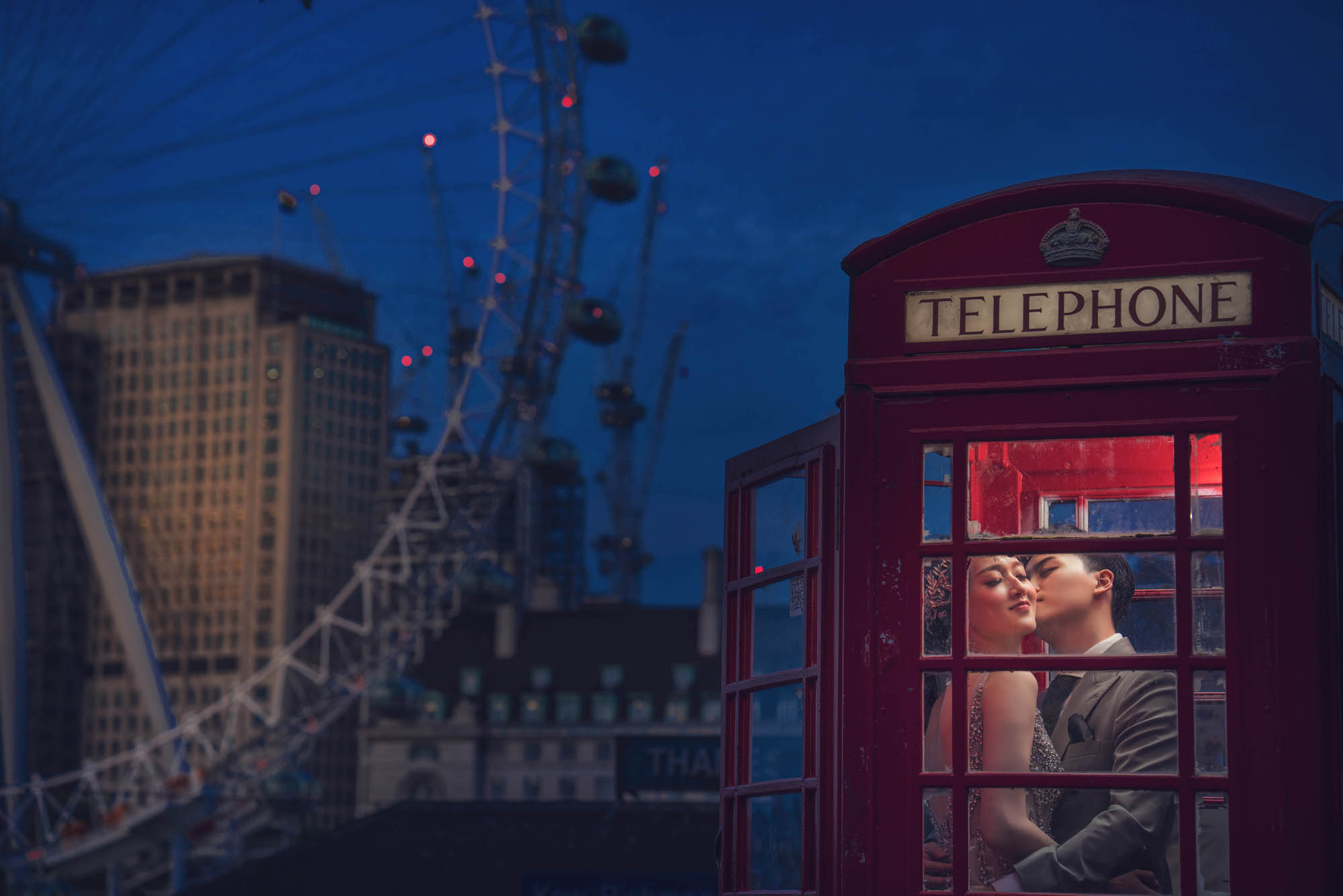 Bride and groom kiss in iconic London phone booth by the London Eye, by CM Leung