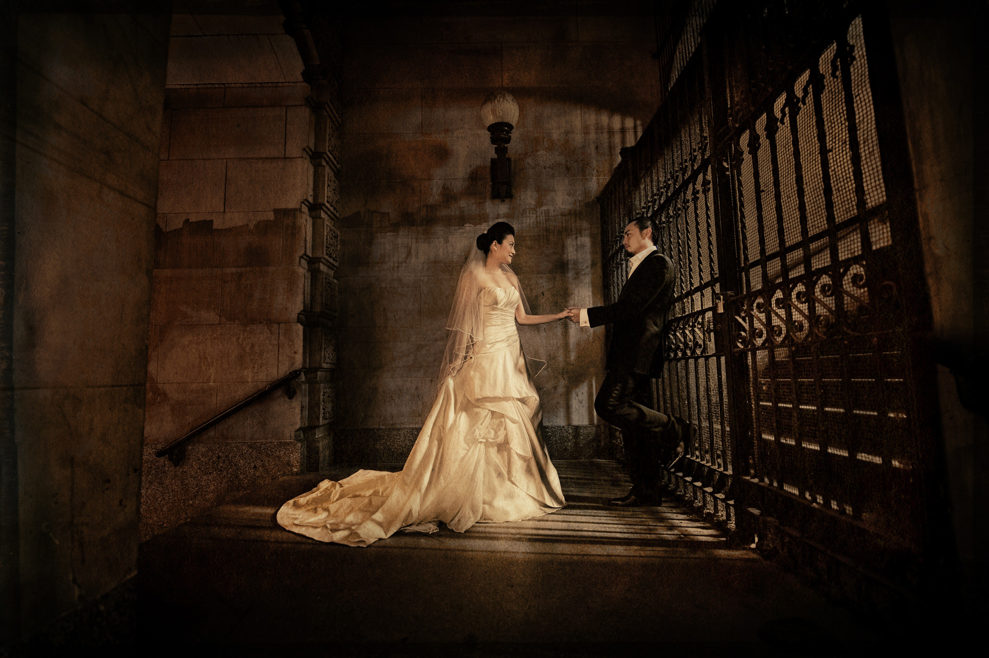 Vintage portrait of bride in satin folded gown with groom on stairs, by Cliff Mautner