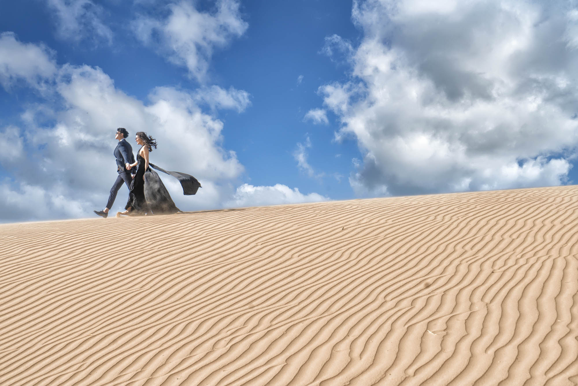 Bride in black gown and groom walking through sand dune, by CM Leung