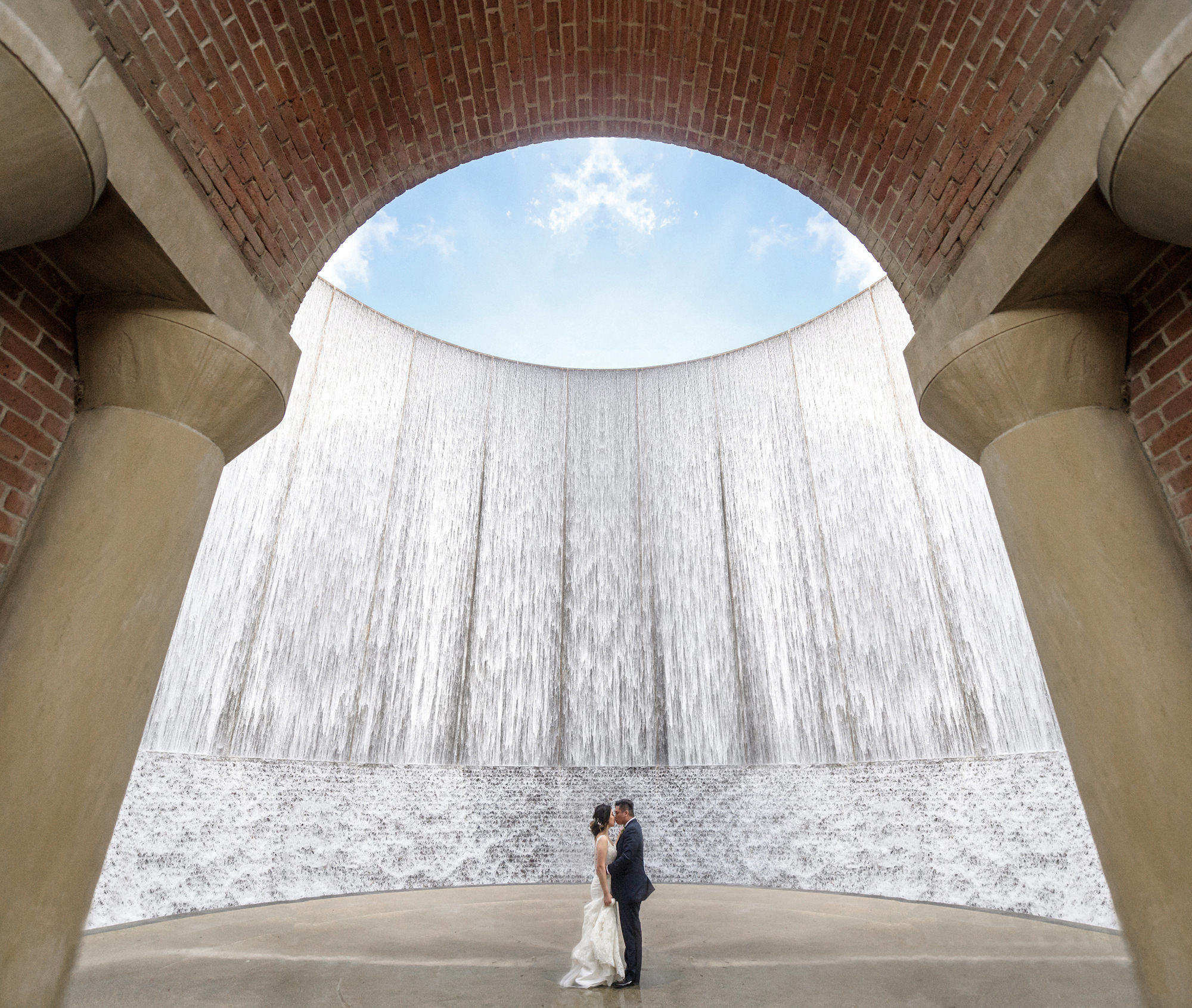 Bride and groom by modern waterfall - photo by 37 Frames - Japan