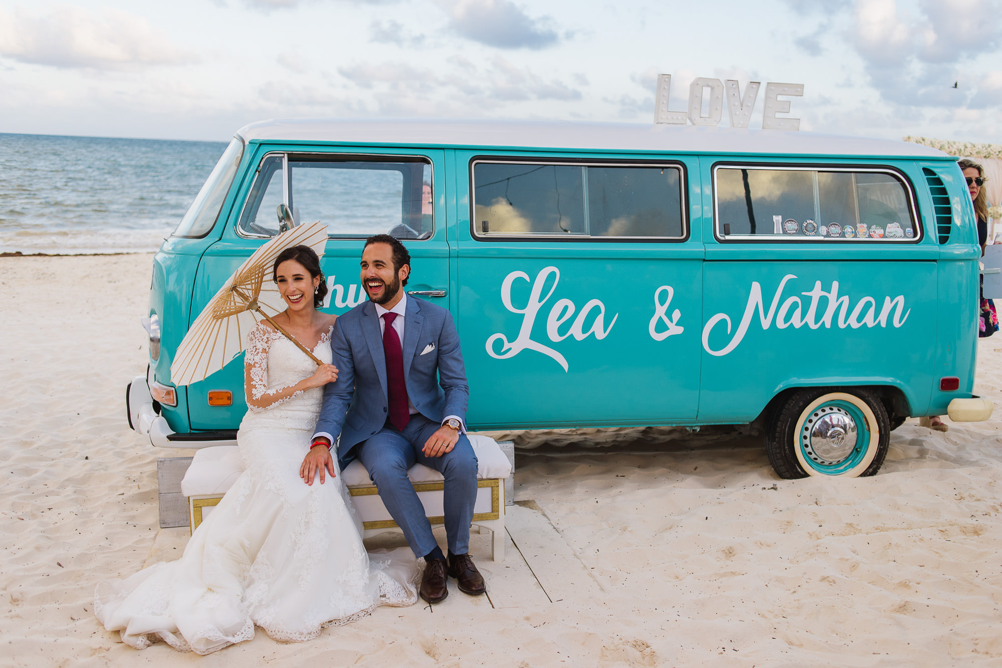 Bride holding parasol and groom sitting in front of Volkswagen van, by Citlalli Rico