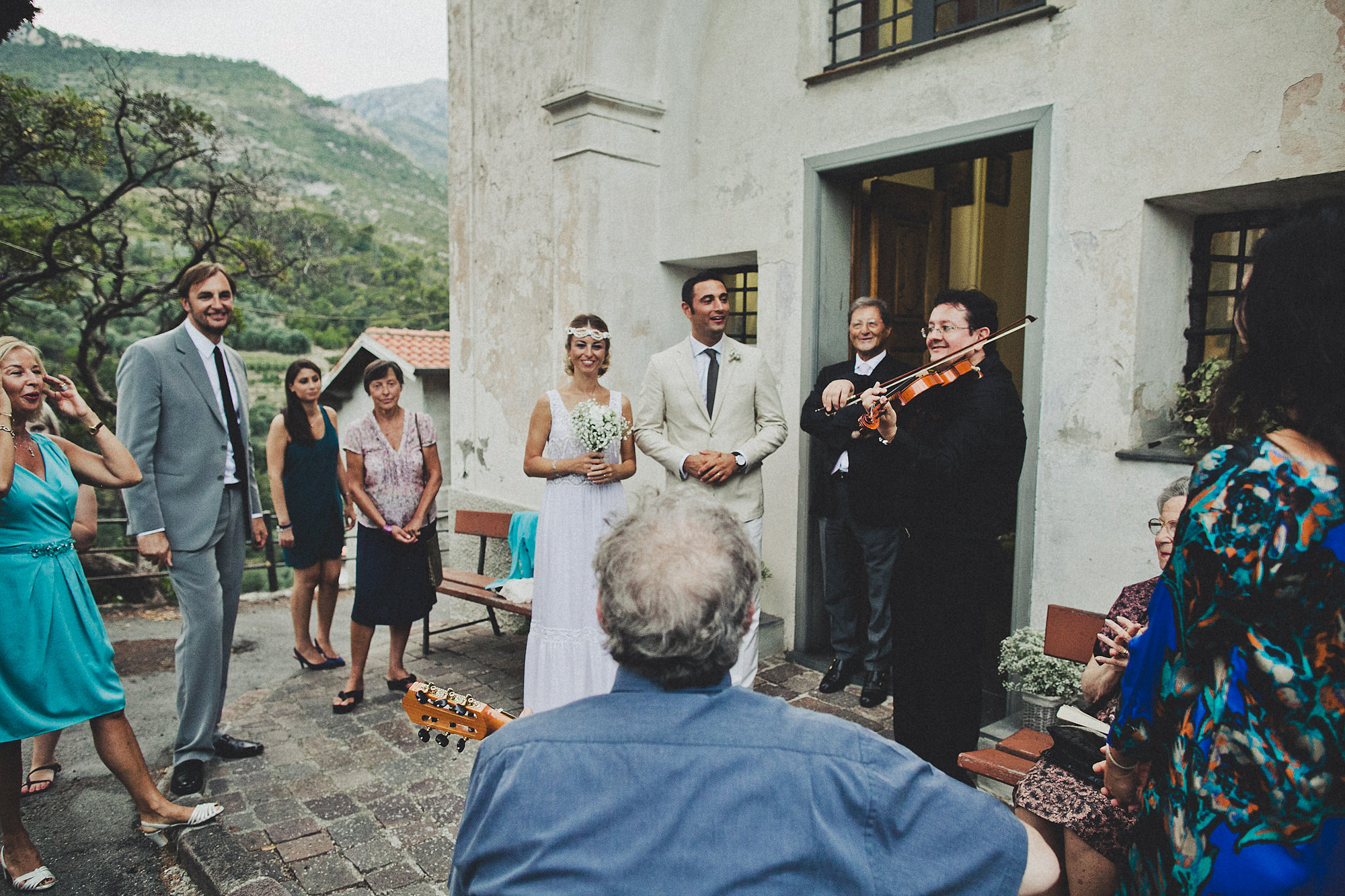 Bride and groom with guests and violinists - photo by Dan O'Day