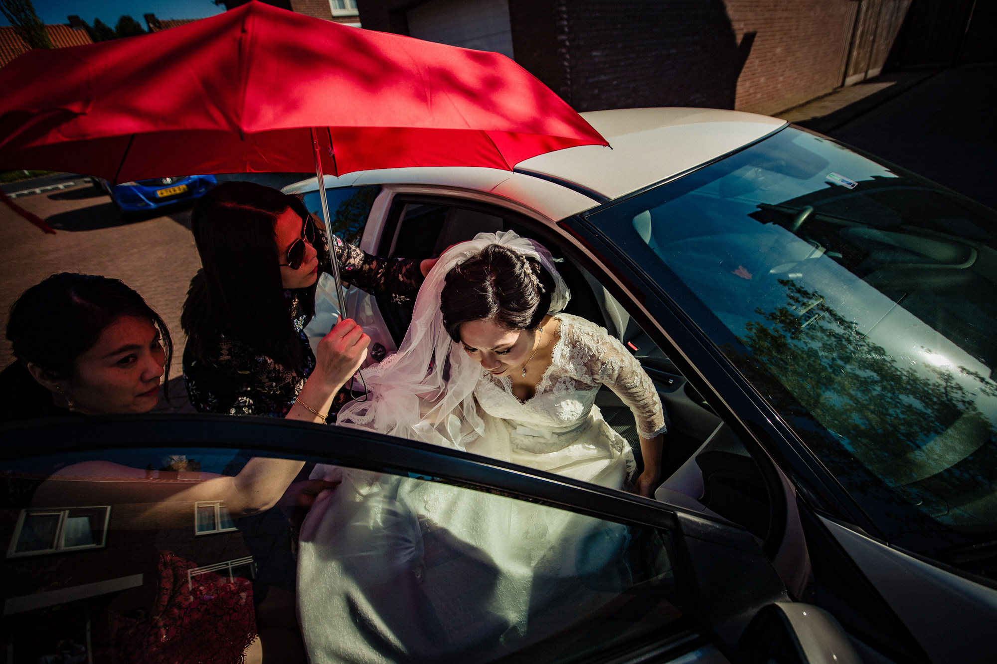 Bride arrives under red umbrella