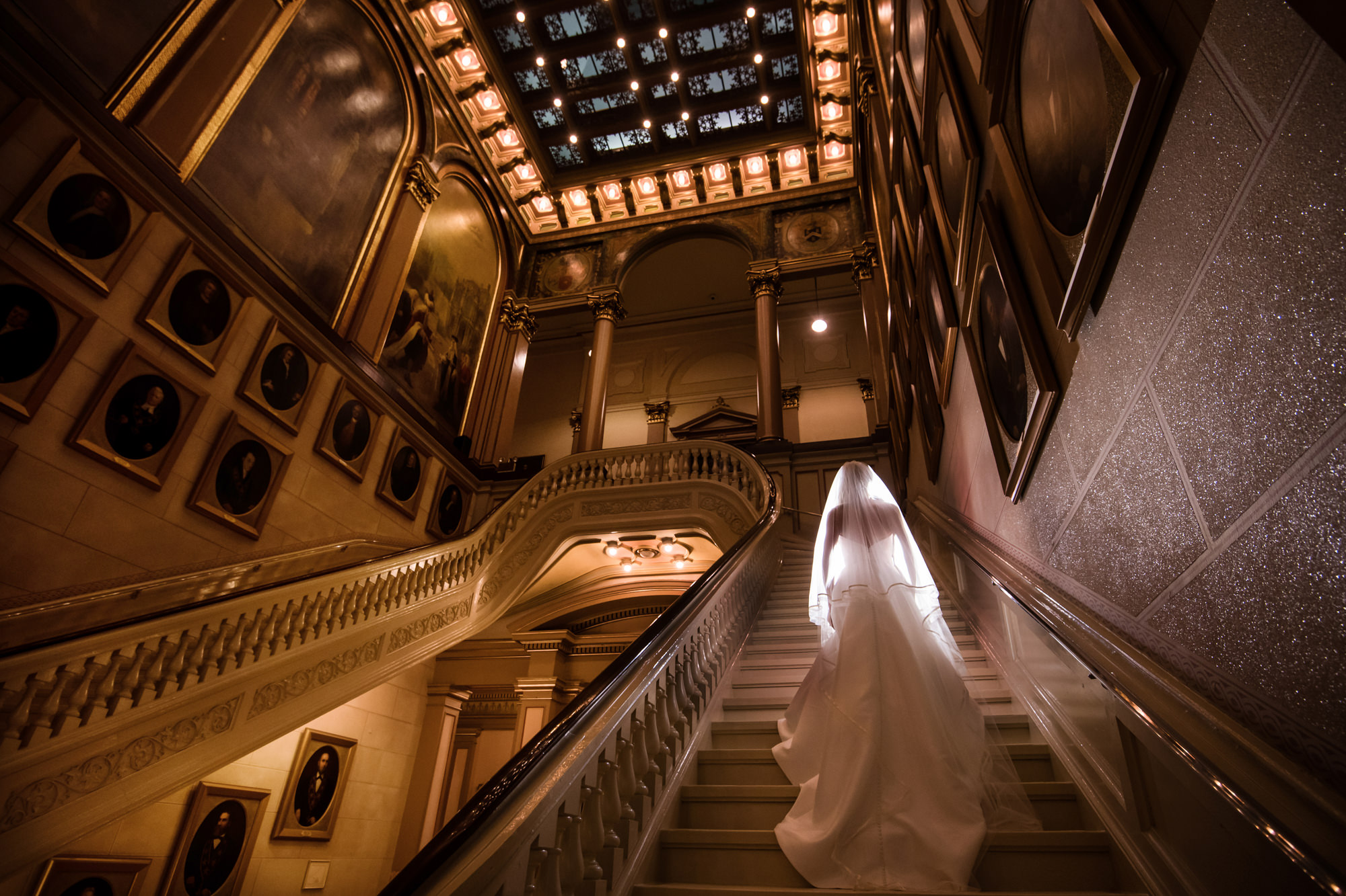 Bride ascending grand staircase in a mansion, by Cliff Mautner