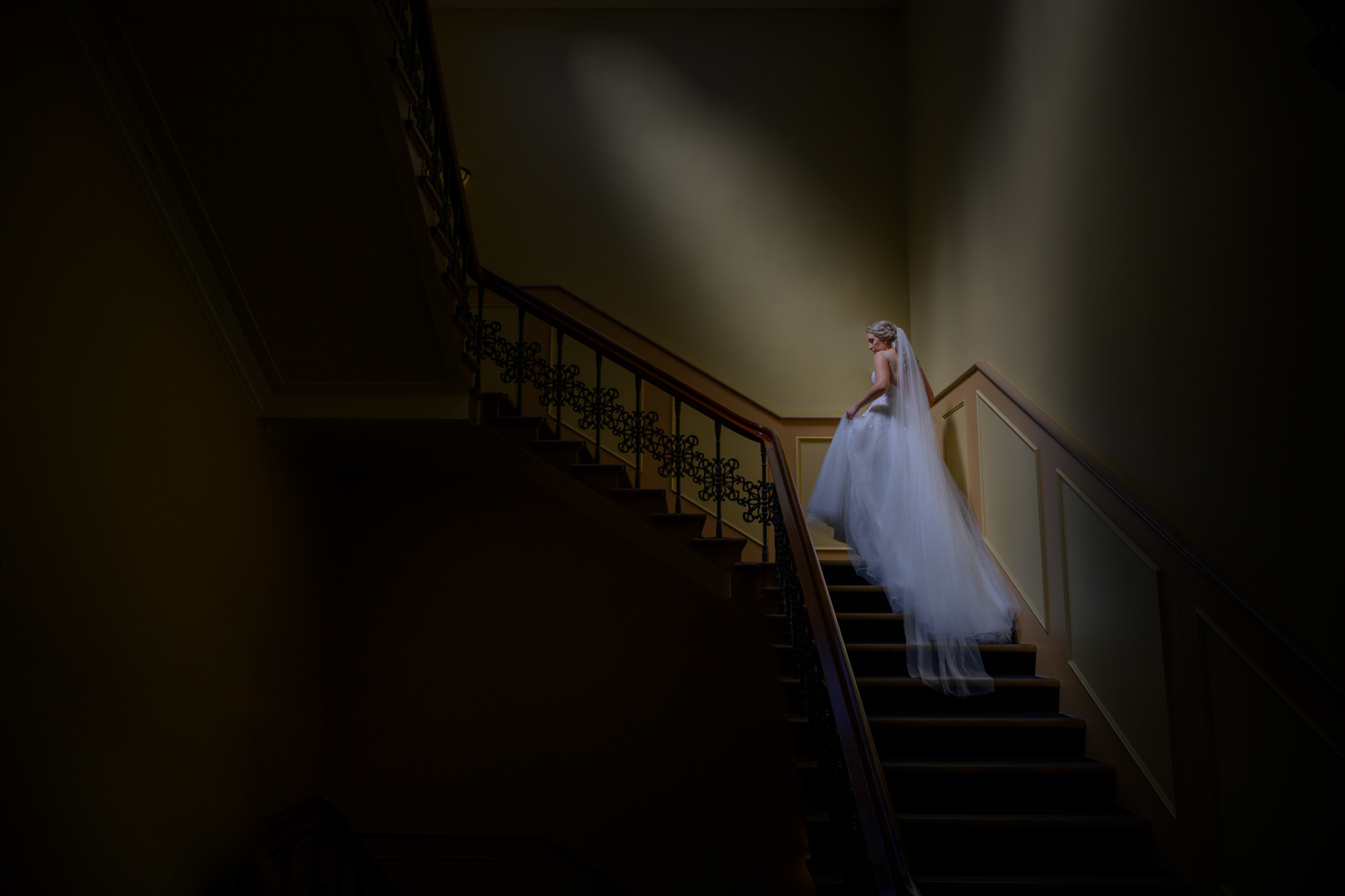 Low light photo of bride ascending stairs with veil - Studio Impressions Photography