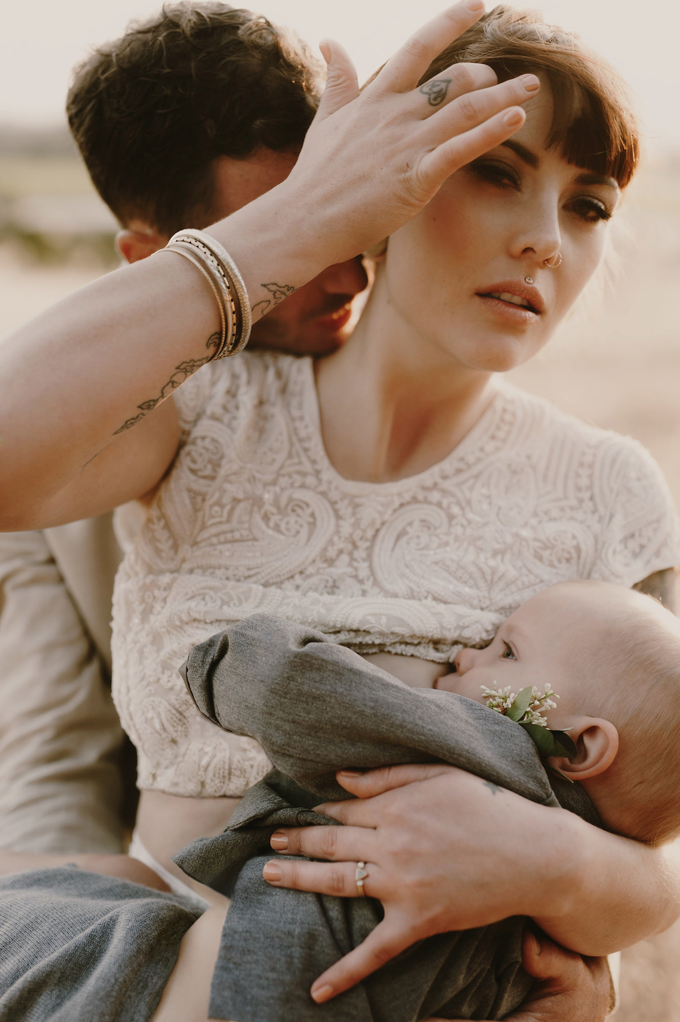 Bride breastfeeds baby while groom kisses her neck - photo by Kristen Marie Parker