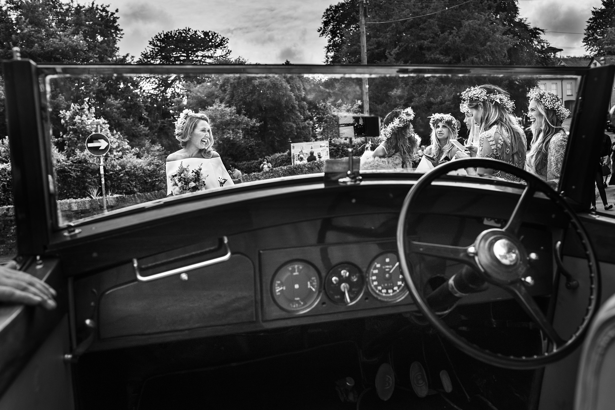 Bride and bridesmaids through windshield of vintage car - photo by Look Fotographia
