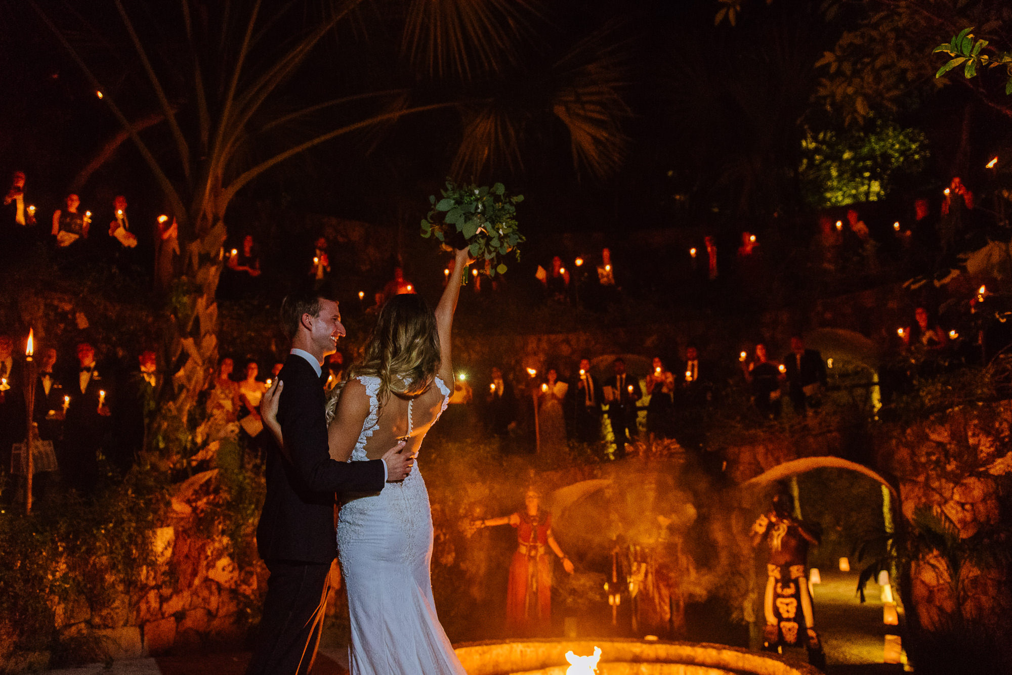 Bride cheers with bouquet in air to guests with groom in candlelit cenote reception, by Citlalli Rico