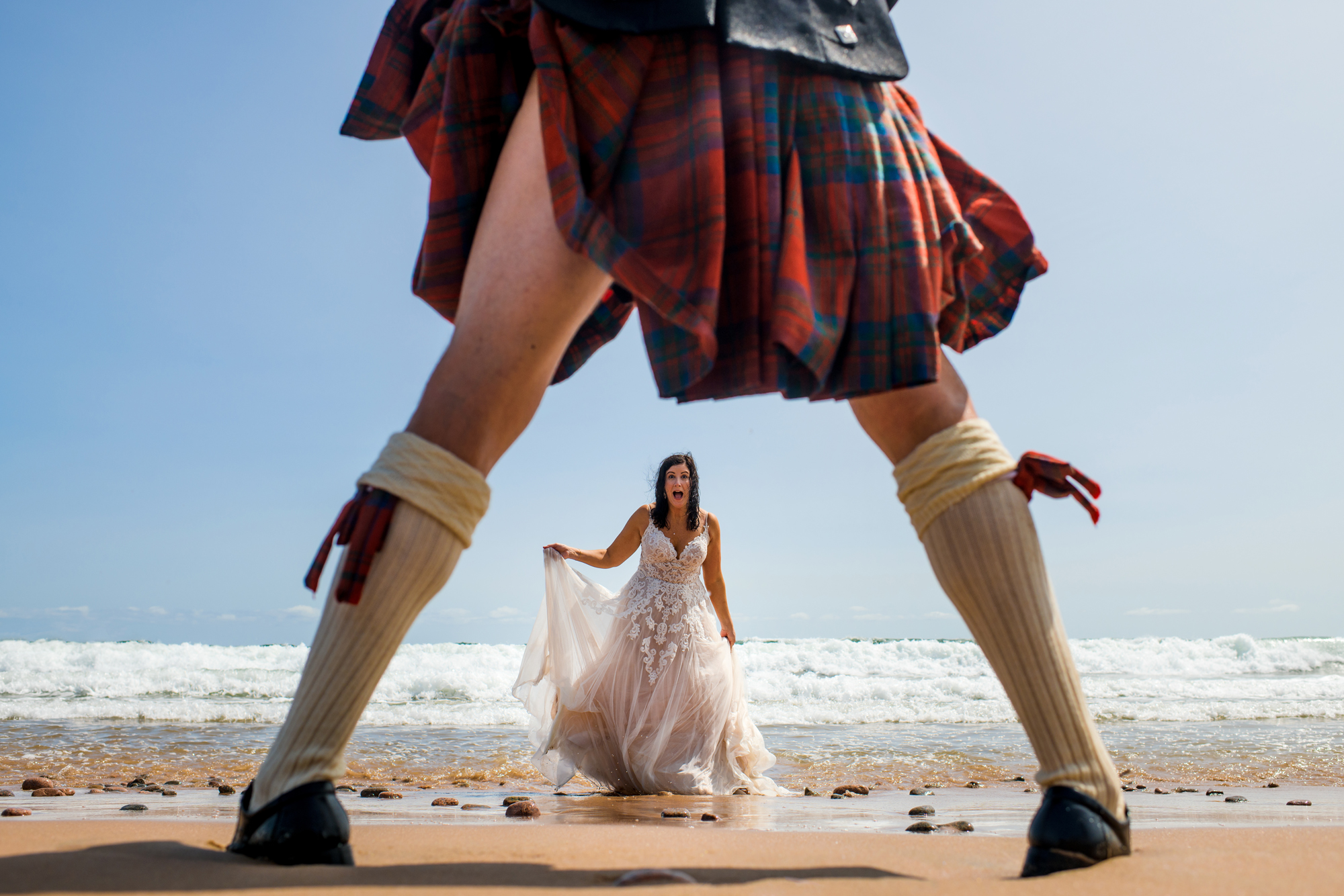 Bride exiting surf, seen from between grooms legs in kilt - photo by Cooked Photography