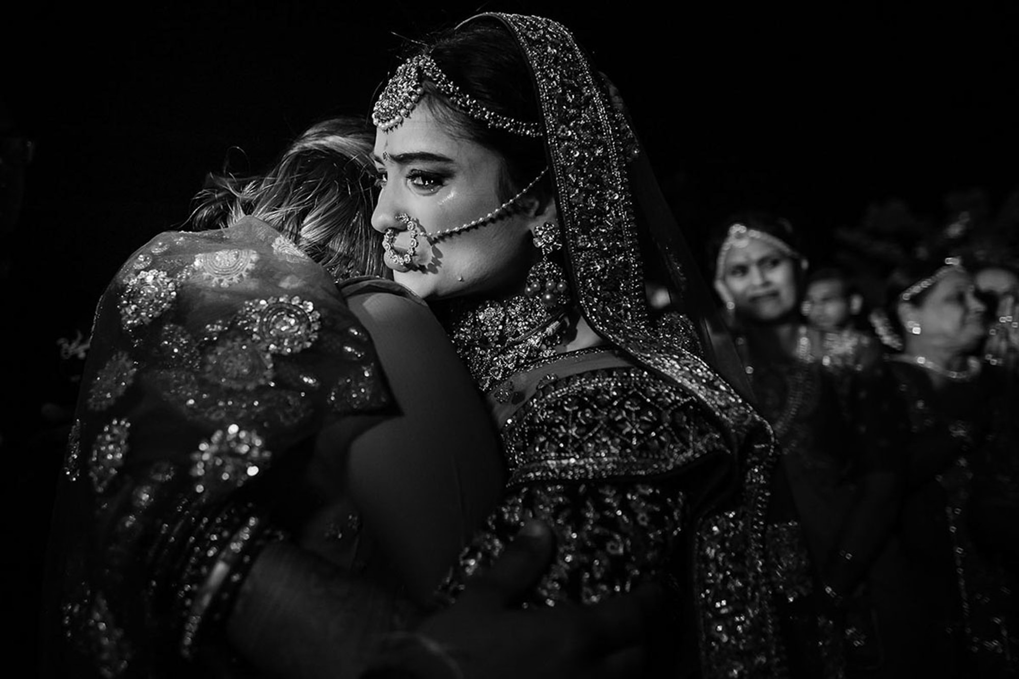 Crying Indian bride hugging her guest - photo by Rimi Sen