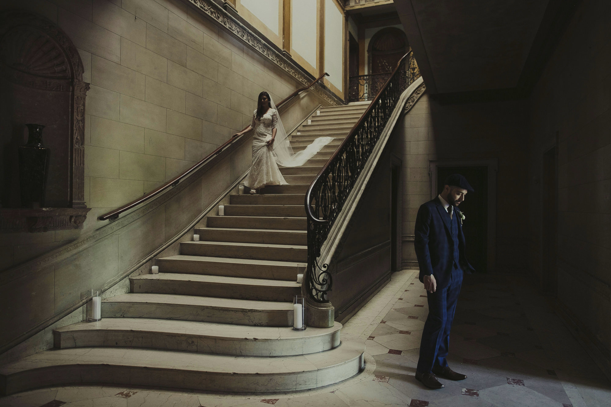 Bride descending stairs to First Look with groom, by Dan O'Day